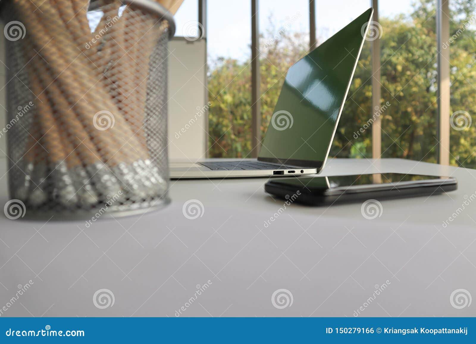 Portátil, telefone celular e lápis na mesa branca