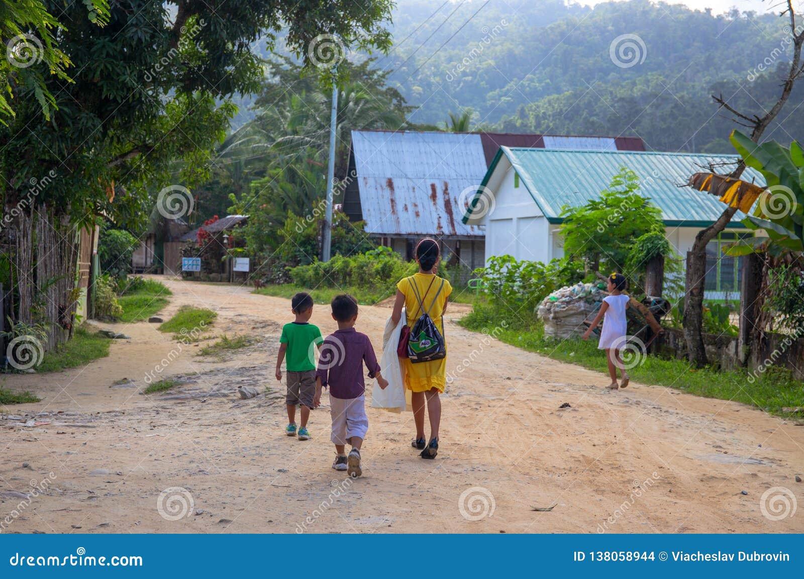 Port-Barton, Philippinen - 23. November 2018: Frau und Kinder auf staubiger Straße Filippino-Familie auf rustikaler Dorfstraße