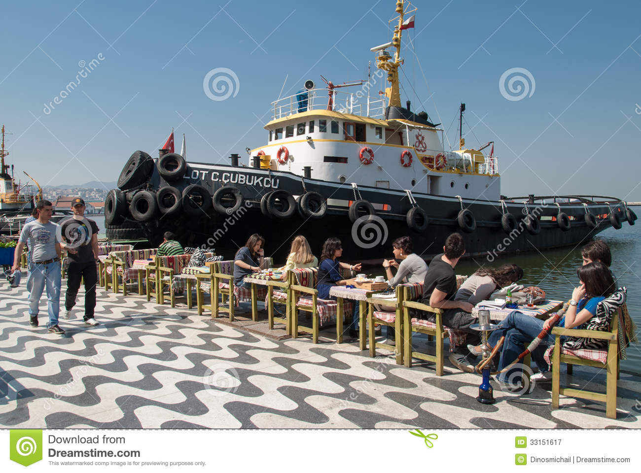 Unidentified young people enjoy the sunshine near a tugboat at the ...