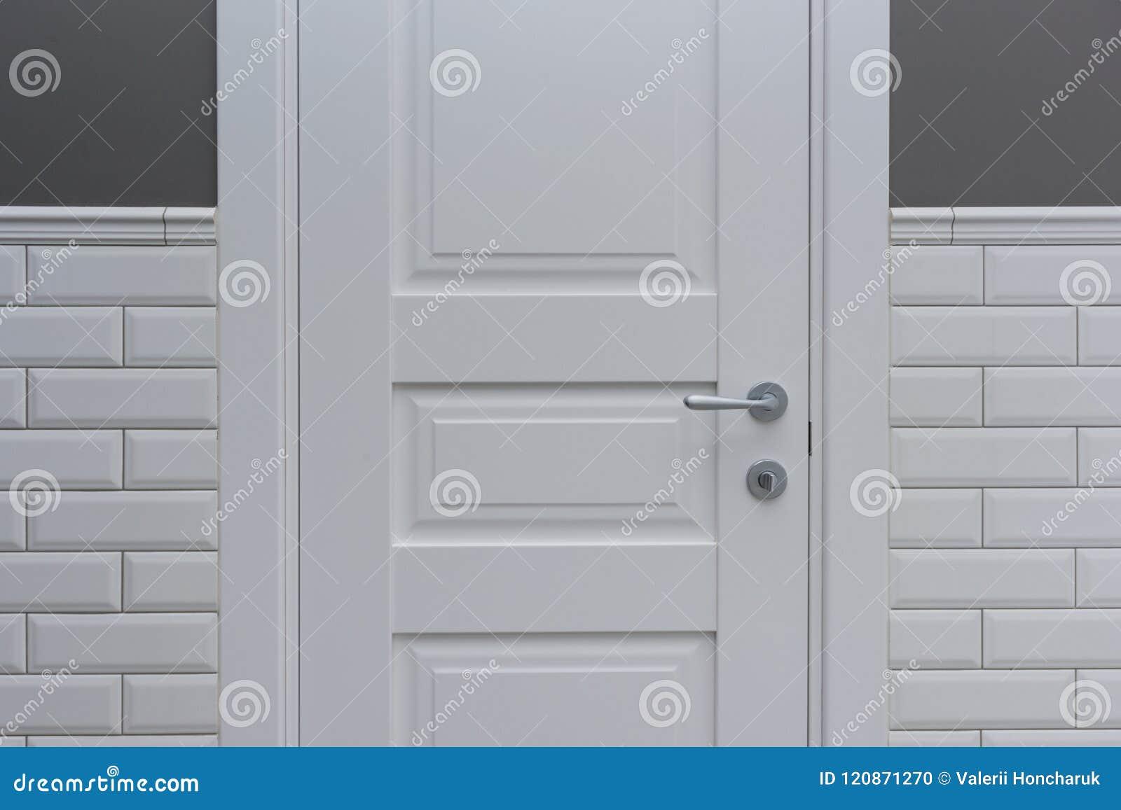 Porta bianca nella stanza della toilette del bagno il gray del
