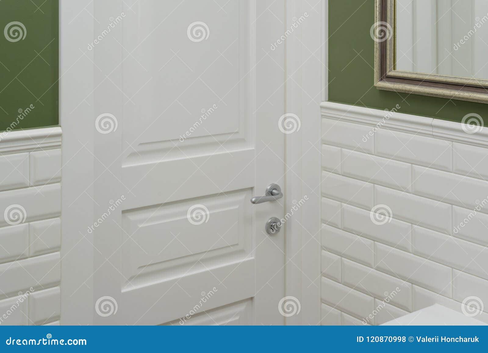 Porta bianca nella stanza della toilette del bagno il verde del