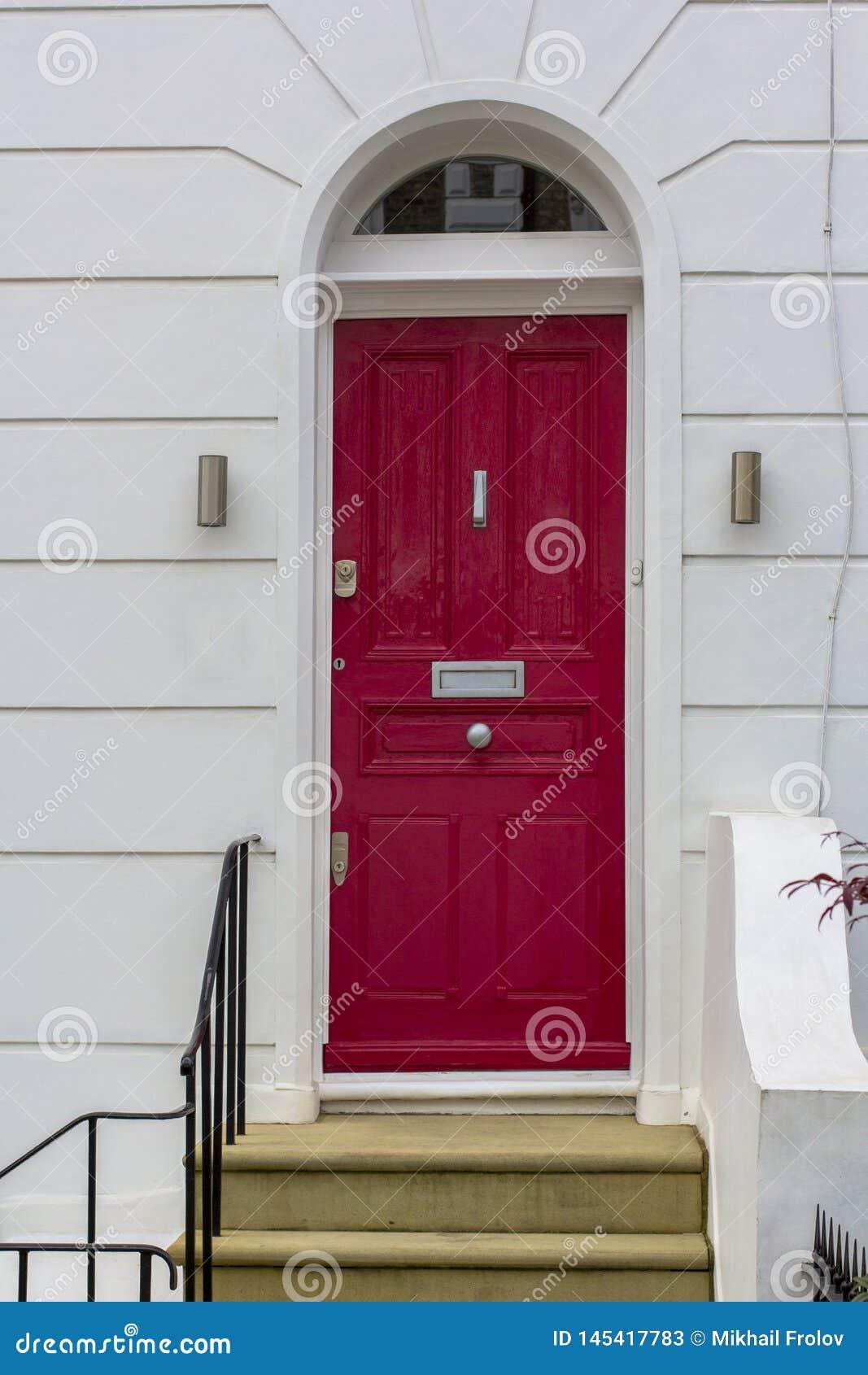 Porta de entrada de madeira vermelha à construção residencial em Londres Porta típica no estilo inglês