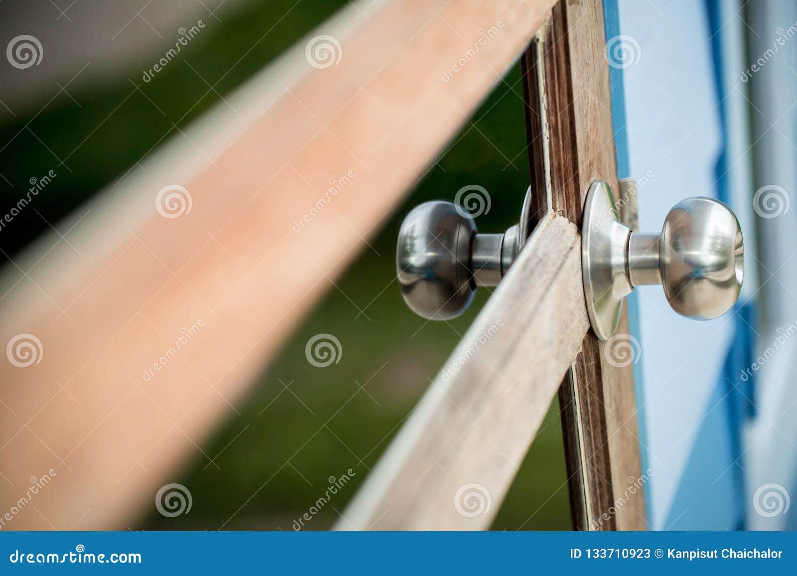 Porta de madeira com grade, o botão de porta inoxidável ou o punho na porta de madeira na iluminação bonita