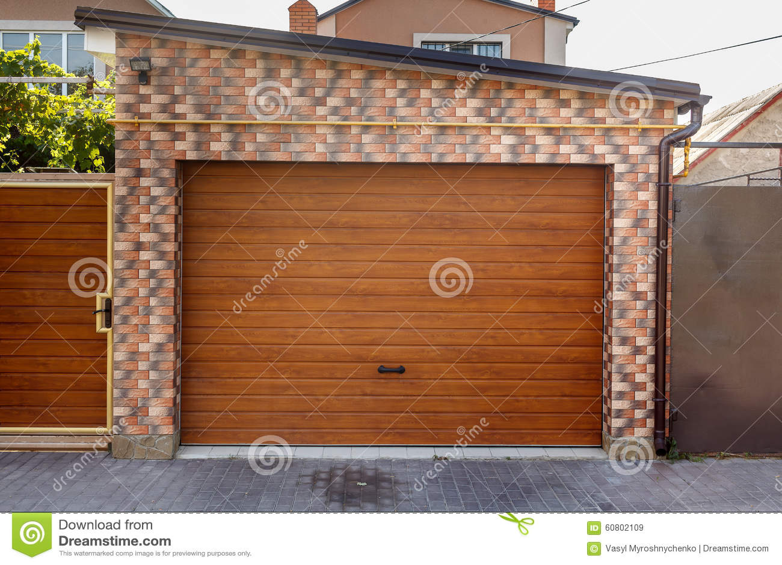 Porta de madeira da garagem com fundo colorido da parede de tijolo