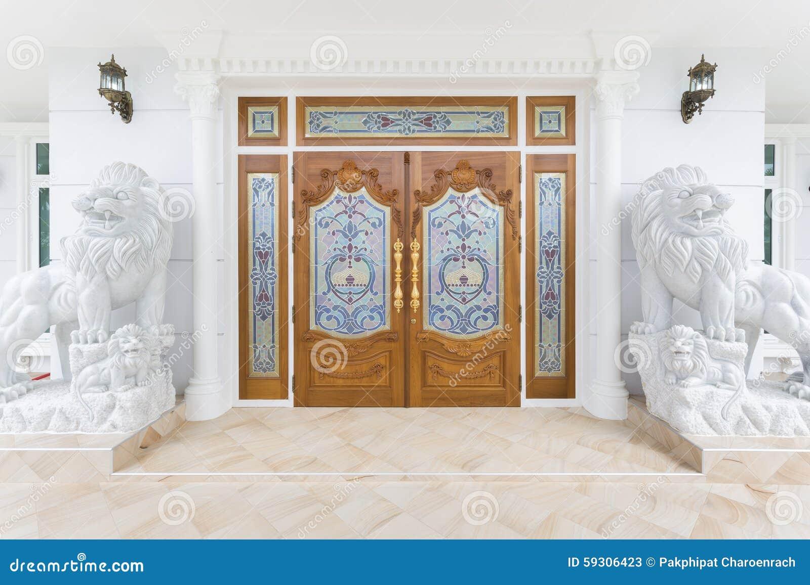 Porta de madeira da teca com a estátua branca dos leões