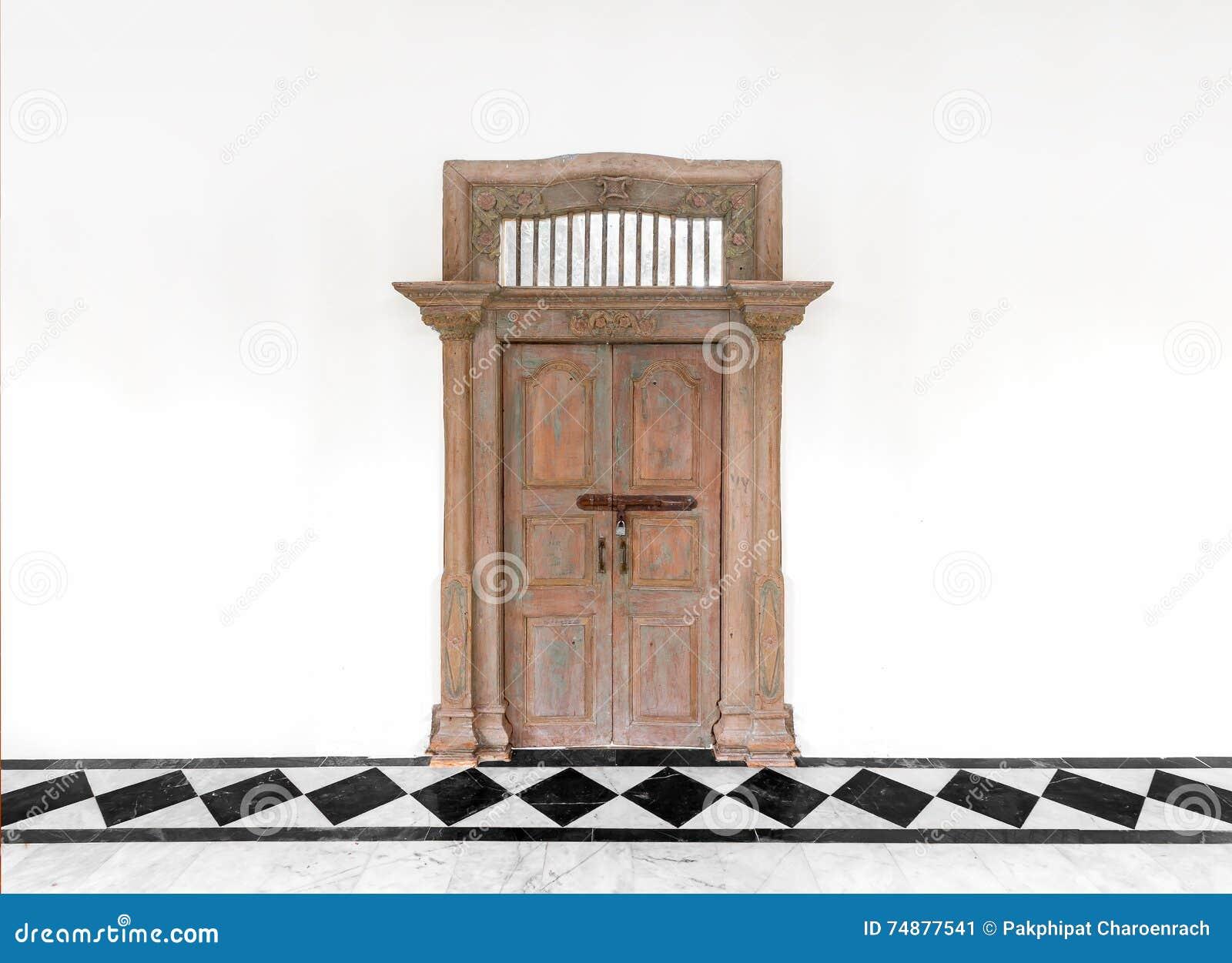 Porta de madeira velha no fundo concreto branco da parede do cimento