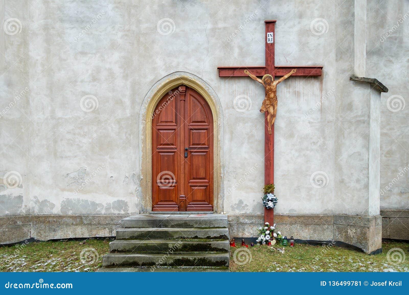 Porta di legno alla chiesa e un grande incrocio sulla parete Quattro candele Tradizione cristiana