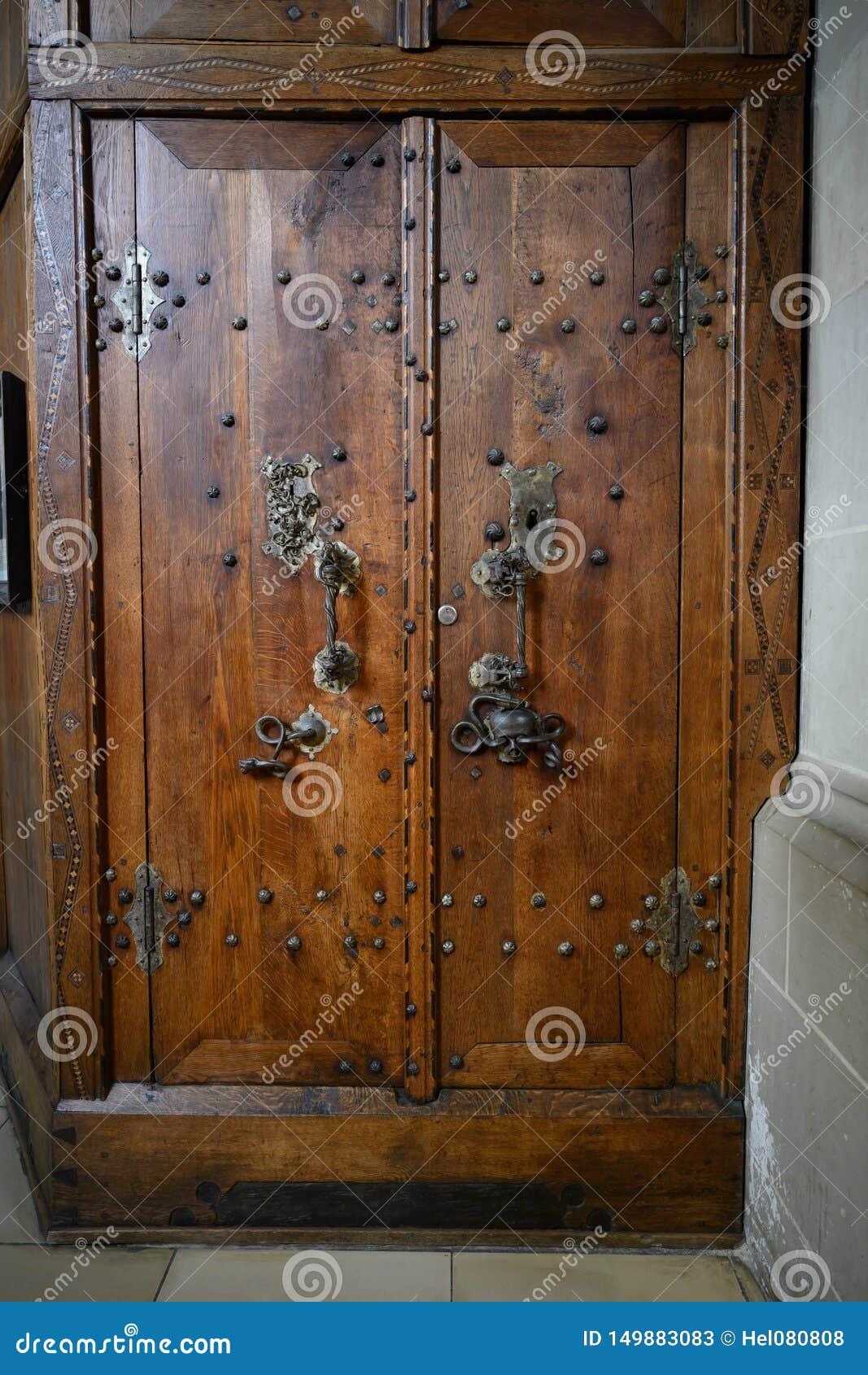 Porta di legno antica della sagrestia con il cranio ed il serpente sul montaggio della porta, san Michael Church Schwabisch Hall,