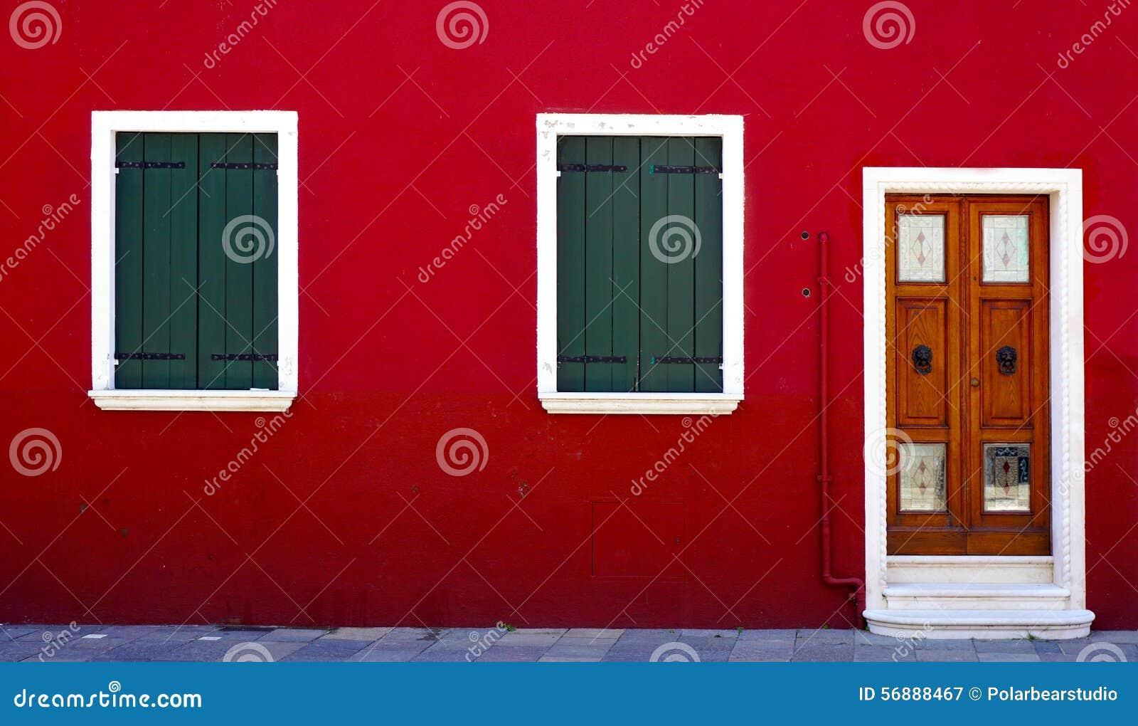 Porta di legno e due finestre sulla parete rossa