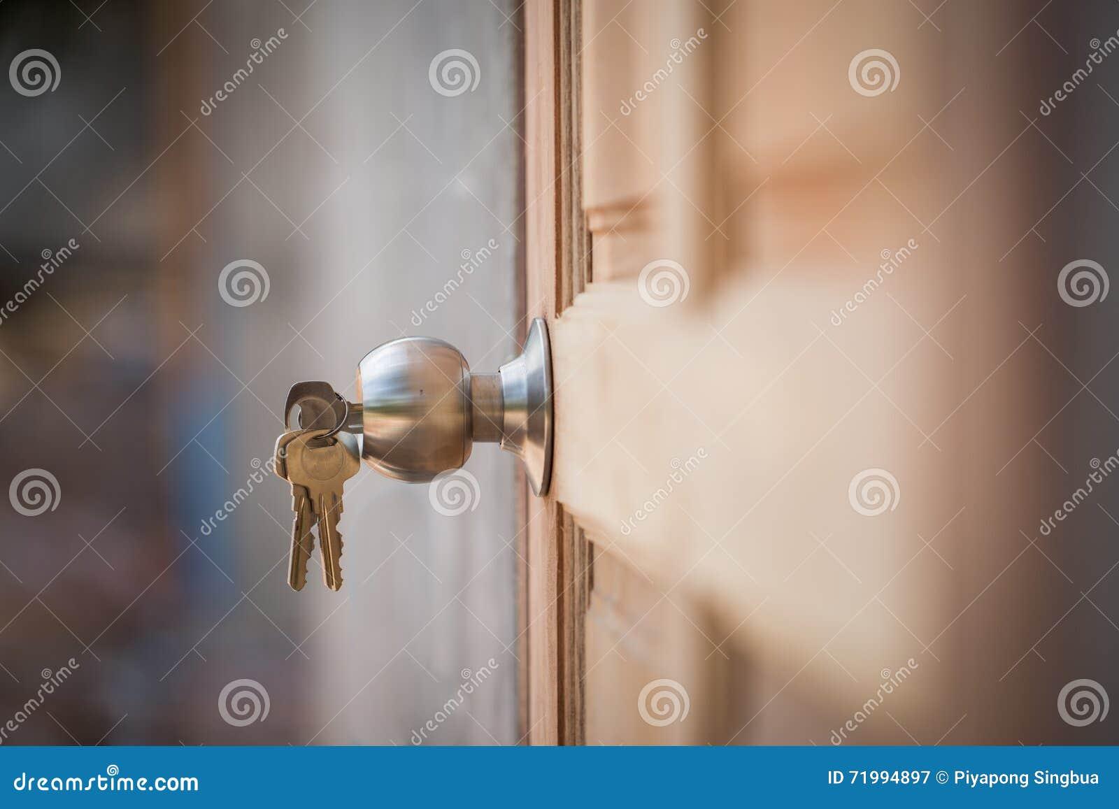 Porta do botão, a chave e a de madeira no fundo cinzento