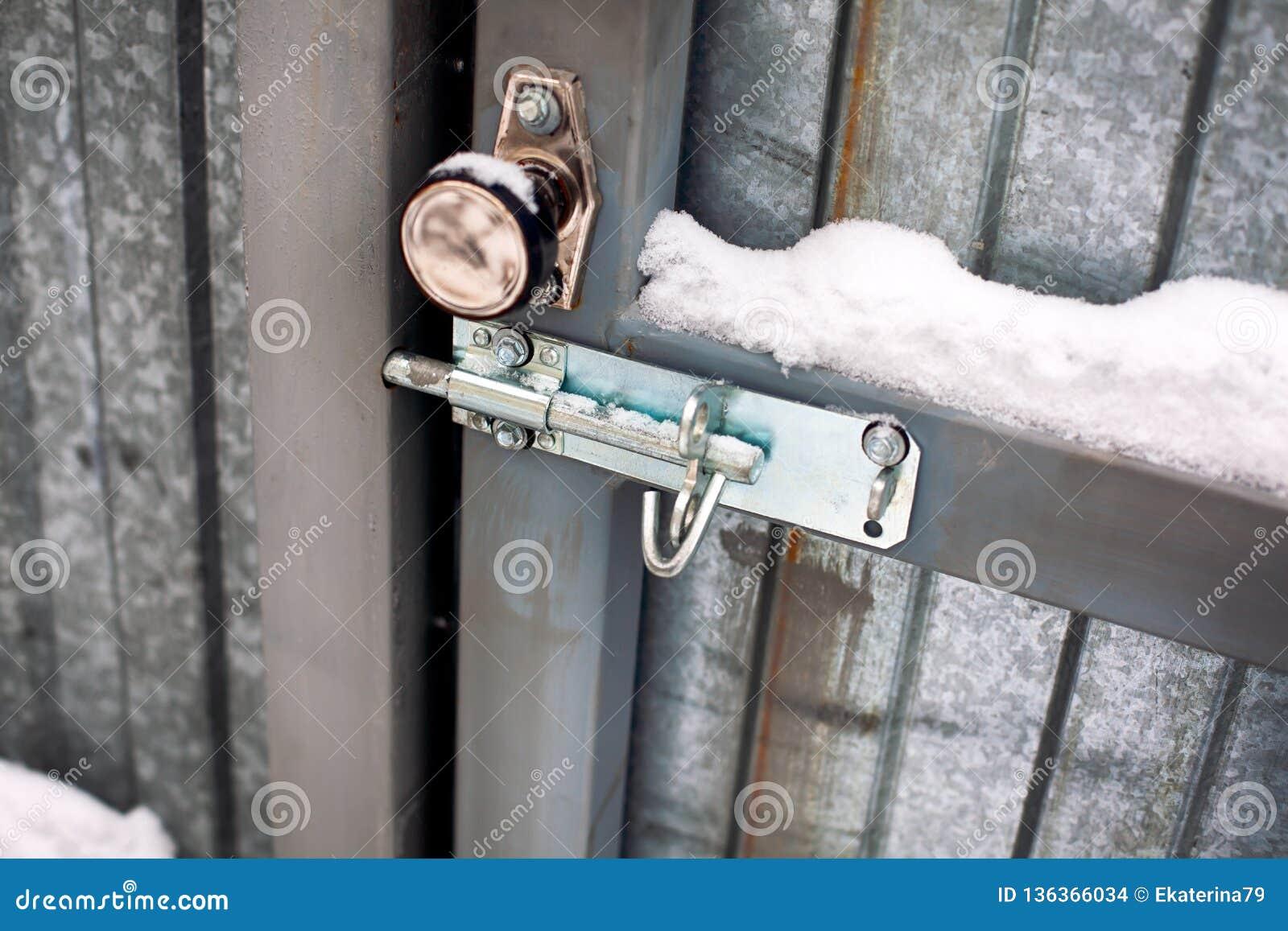 Porta do metal com botão de porta e para aparafusar a neve coberta