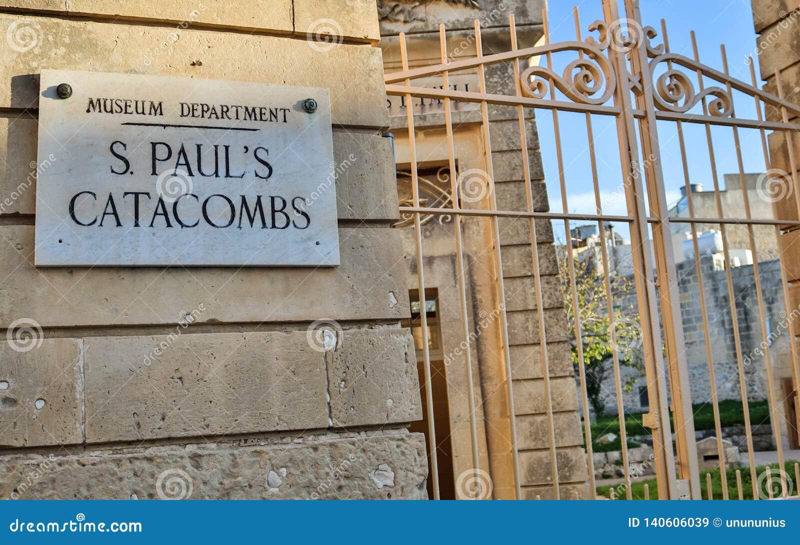 A porta fechado da entrada com sinal às catacumbas e ao museu do St Paul em uma parede do arenito