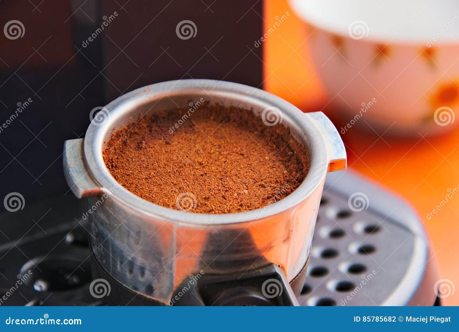 Porta filter med nytt jordkaffe som är klart att brygga i espressomaskinen