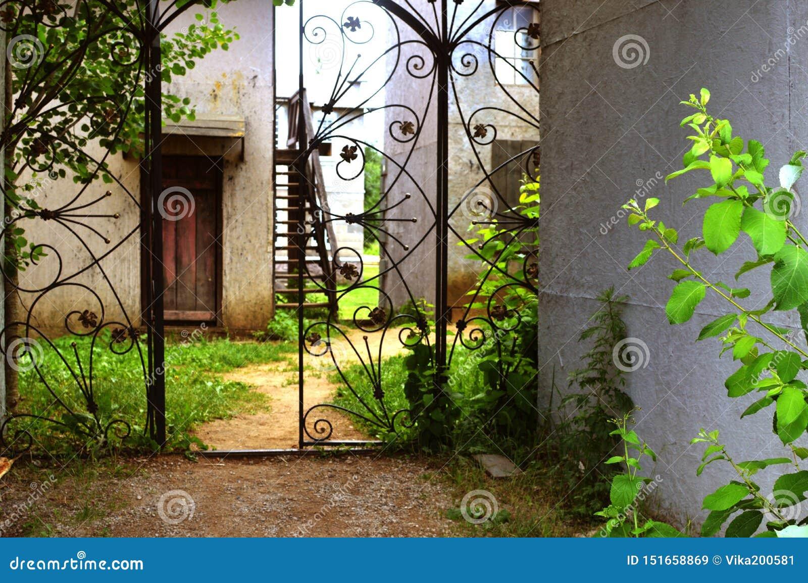 A porta forjada velha em um jardim