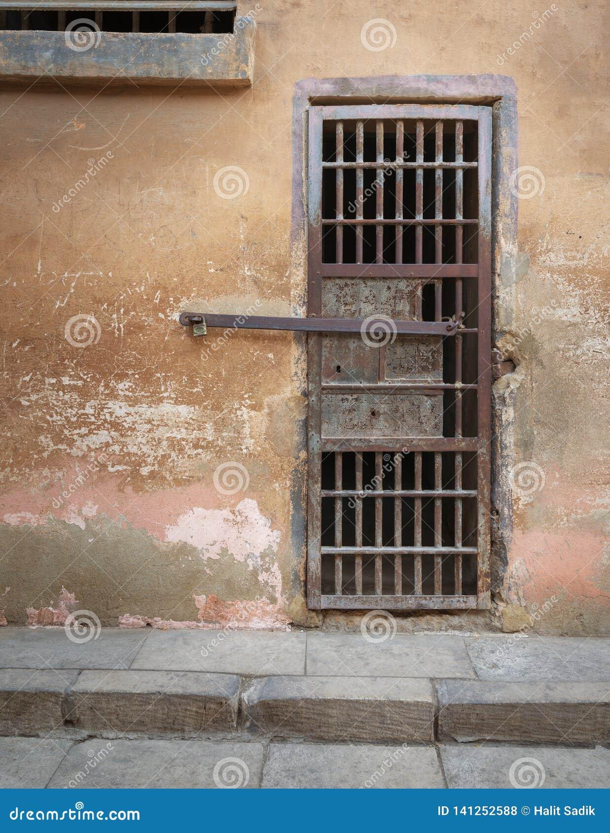 Porta oxidada Closed da pilha das barras de ferro e parede de pedra resistida do grunge na prisão abandonada fechado