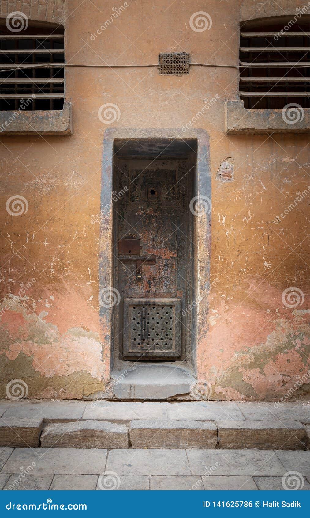 Porta oxidada Closed da pilha do ferro e parede de pedra resistida do grunge na prisão abandonada fechado, citadela do Cairo, Egi