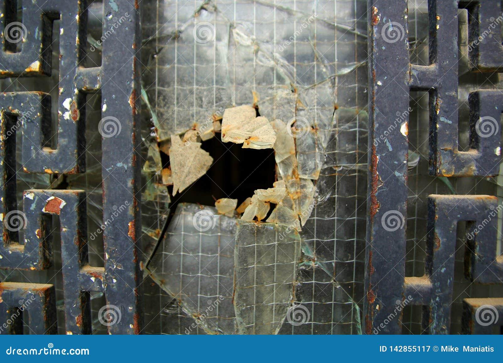 Porta oxidada velha com o vidro quebrado