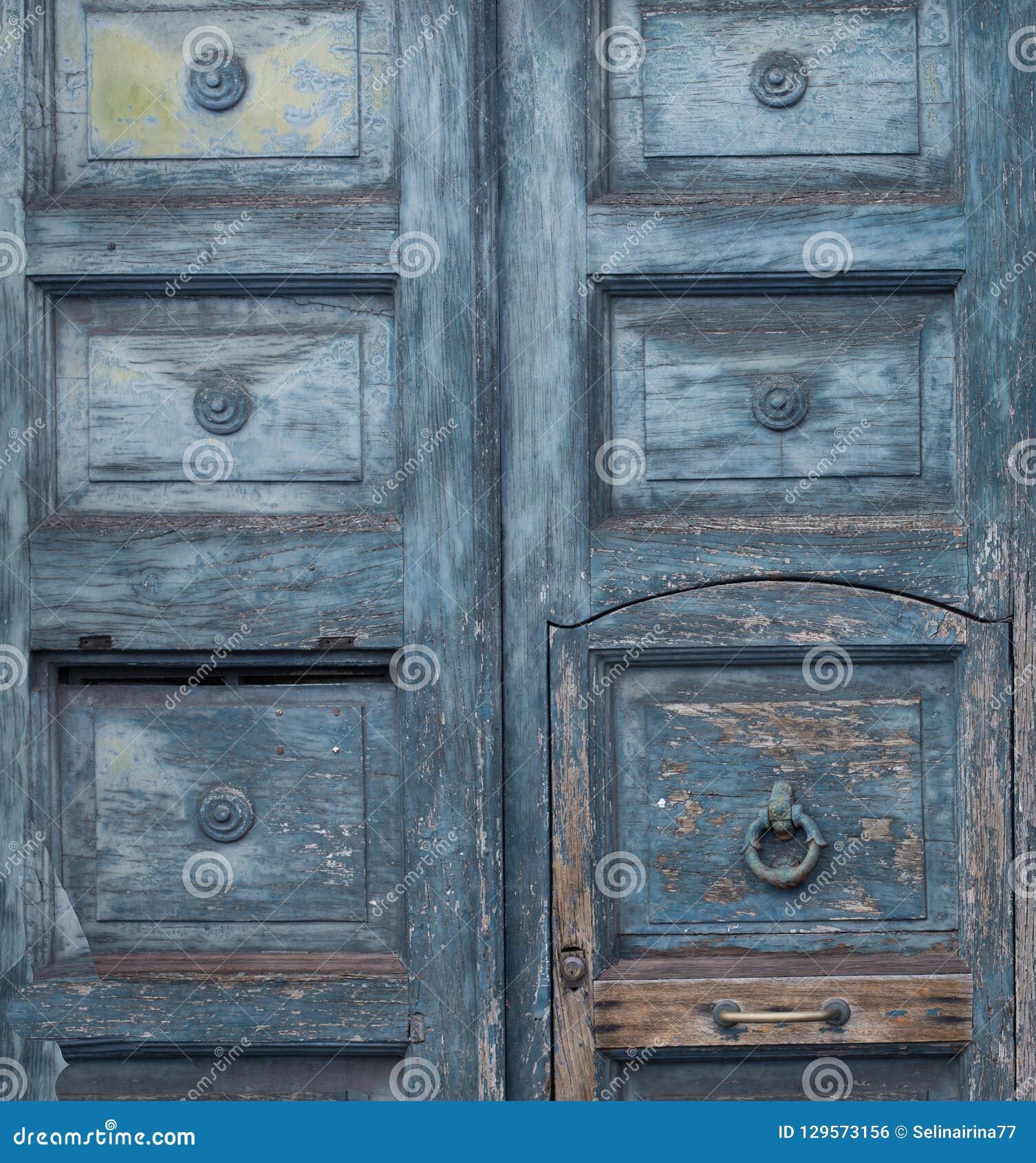 Porta velha azul com pintura rachada e um botão do vintage para bater na porta sob a forma de um anel