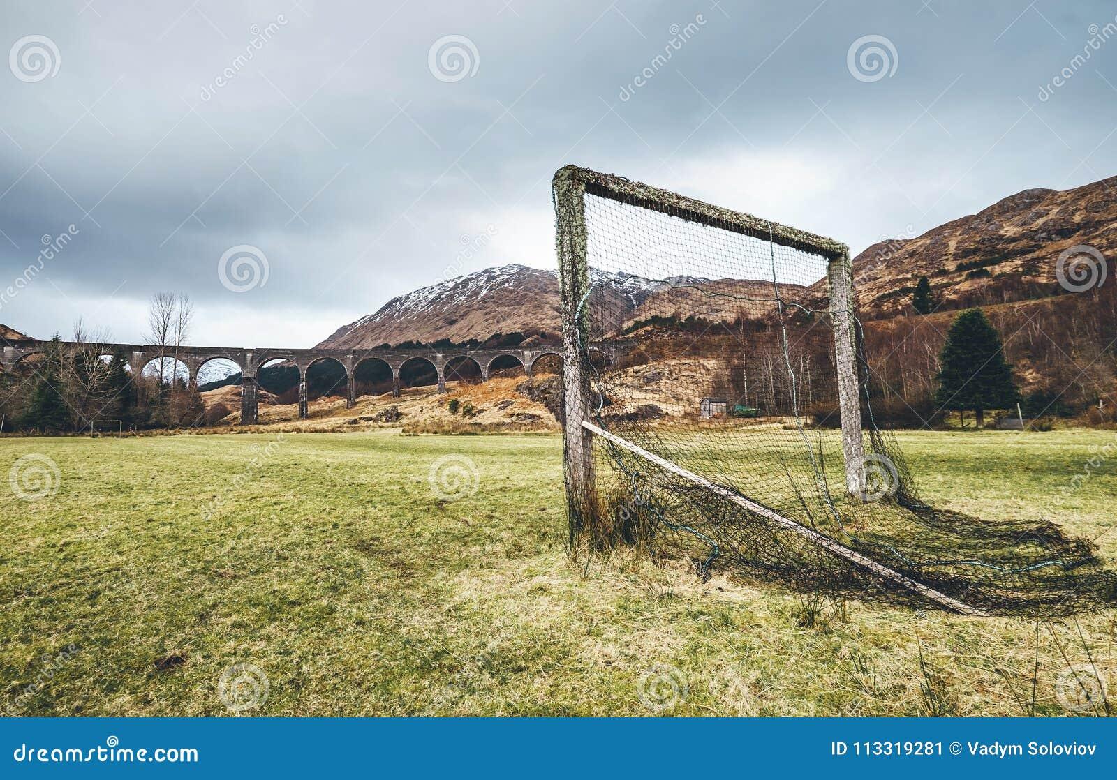 Porta velha do futebol no campo de jogos da grama verde perto do viaduto famoso de Glenfinnan em Escócia, Reino Unido