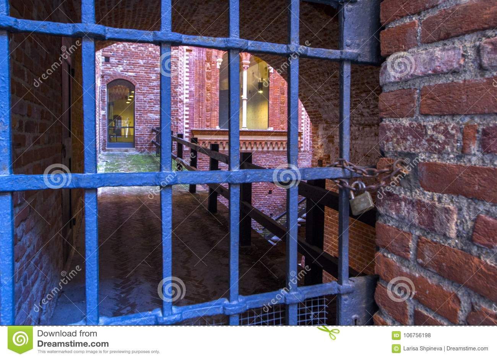 Porta velha na fortaleza, abertura velha do Dungeon da grade do ferro Concepção arquitetónica de pedras e de tijolos, alvenaria v