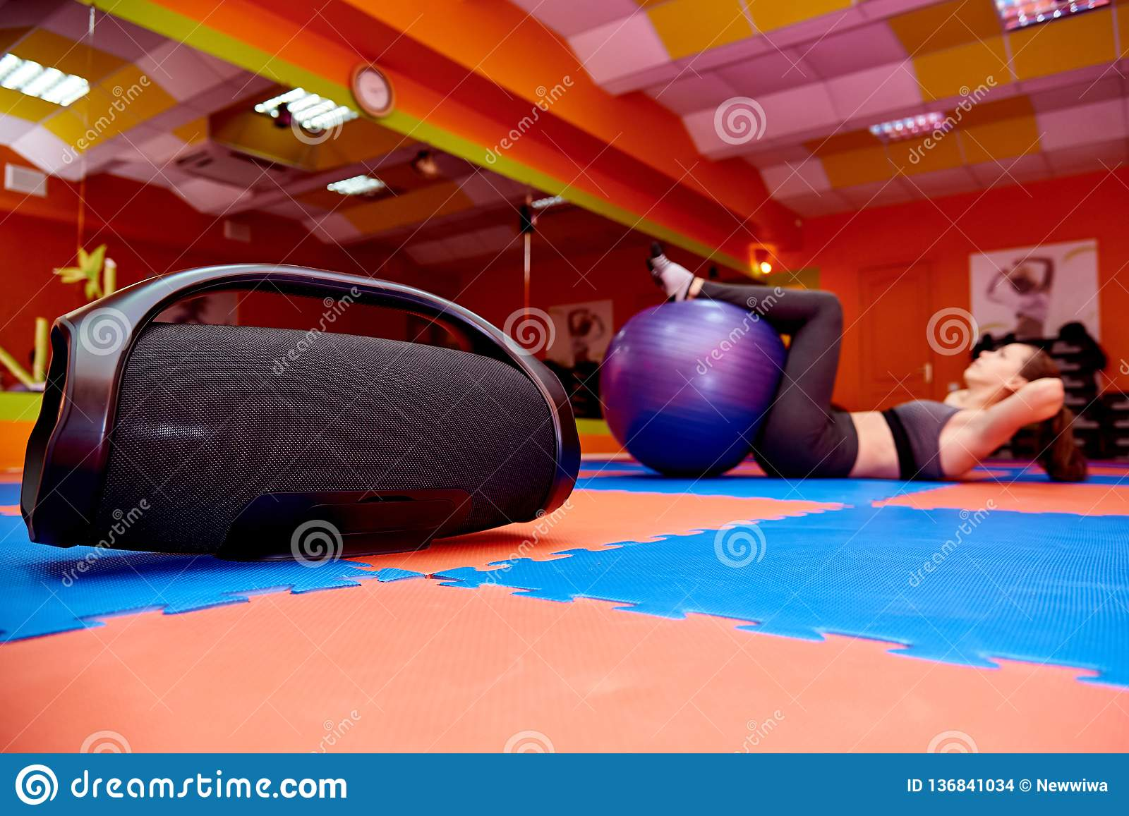 Portable acoustics in the aerobics room on the background of a blurred girl practicing sport