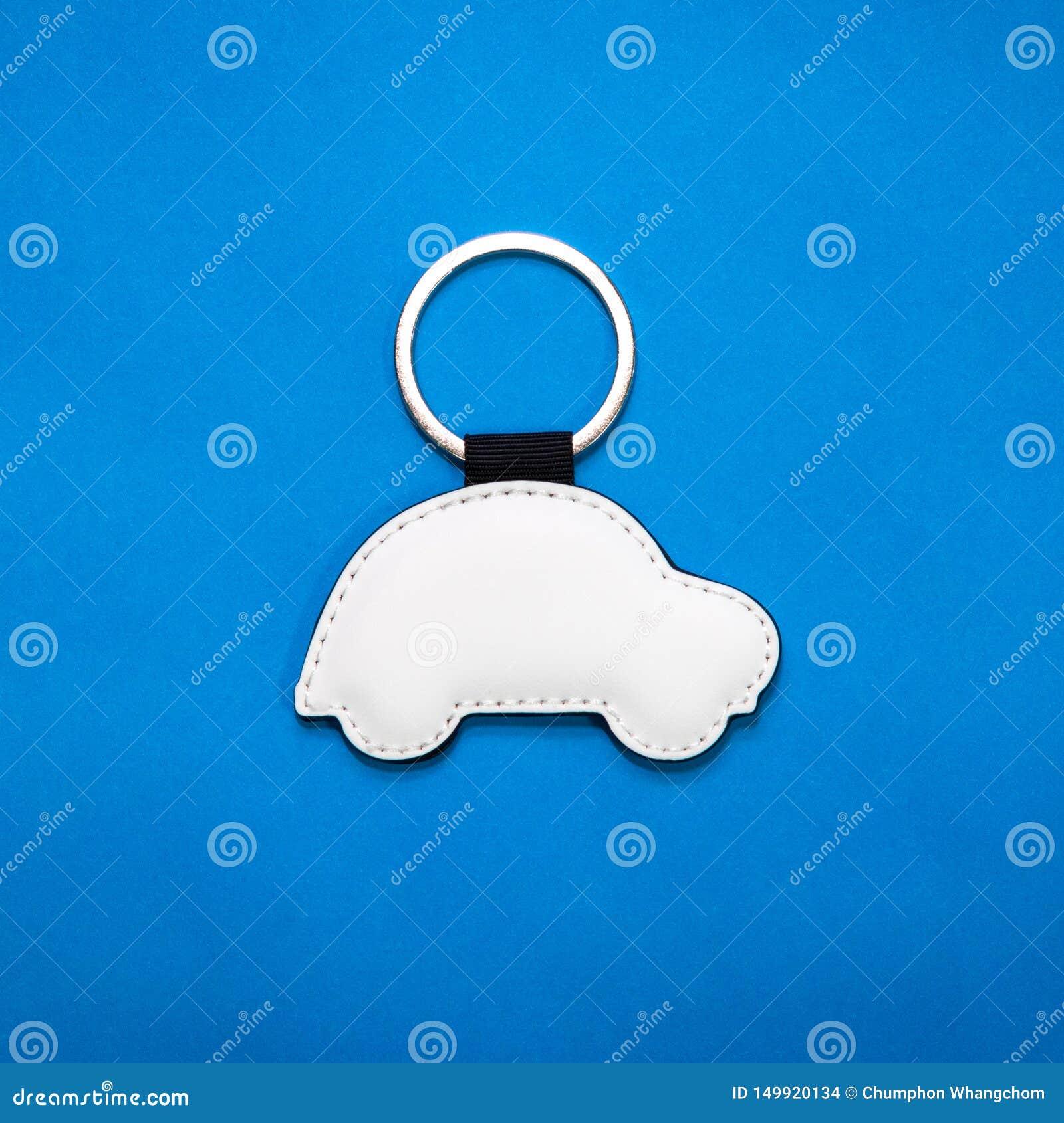 Portachiavi a anello di cuoio nella forma dell automobile su fondo di carta blu Catena chiave in bianco per la vostra progettazio