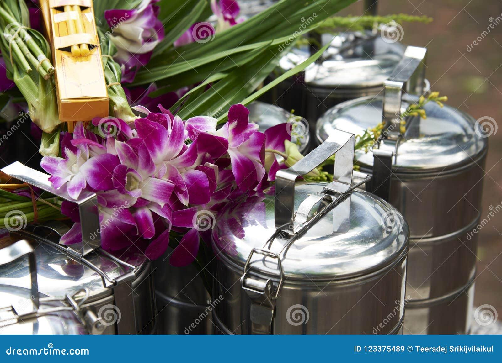 Portadores de la comida que ofrecen a los monjes y a las orquídeas
