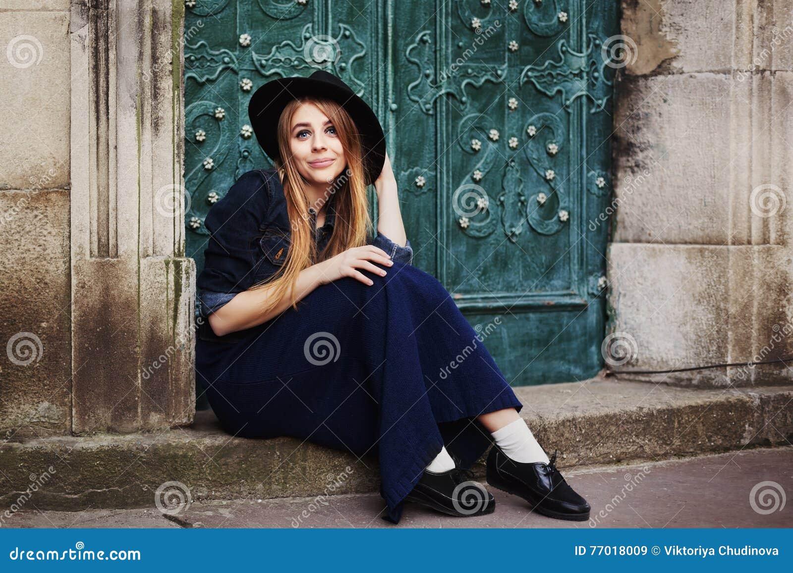 Portait completo del cuerpo de la calle de la mujer joven sonriente stilylish que se sienta cerca de la puerta Looking modelo en