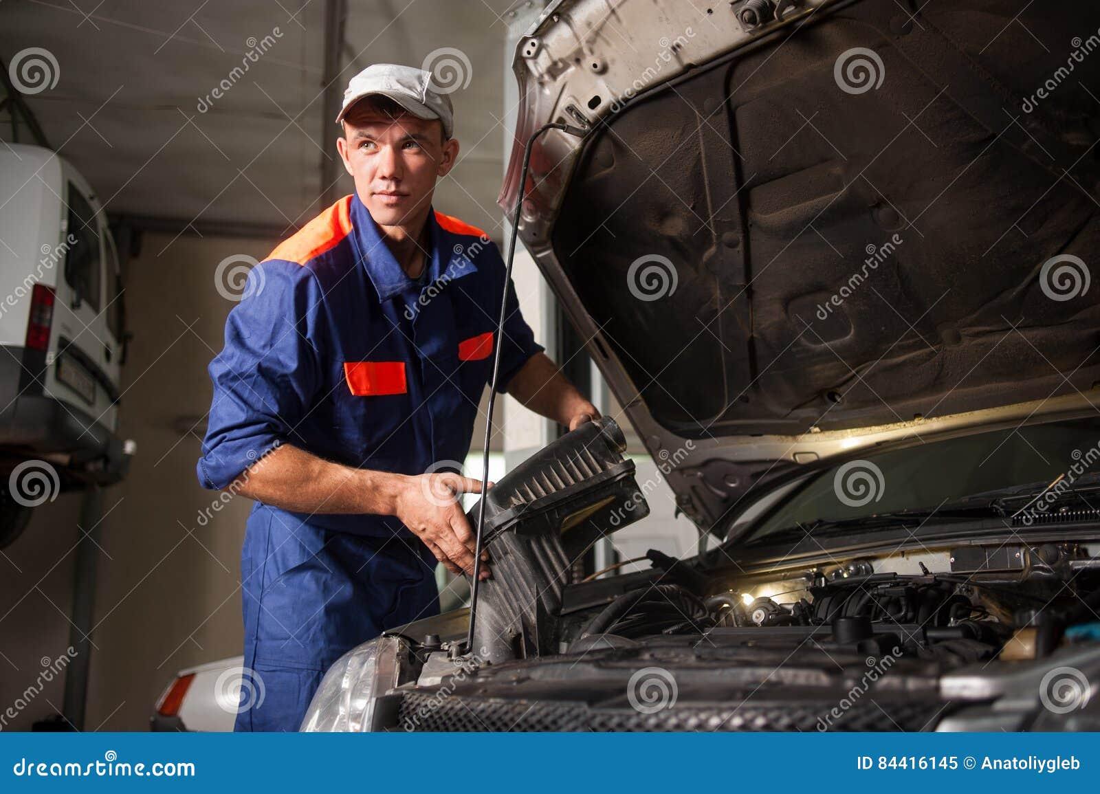 Portait do motor de automóveis da fixação do mecânico na oficina de reparações