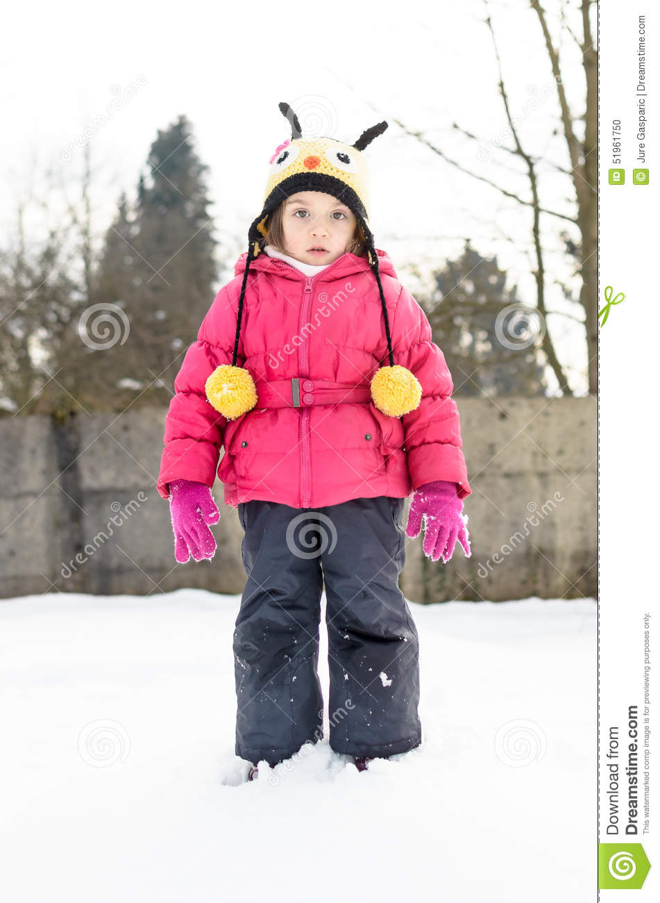 portait of a little girl in winter clothes having fun in