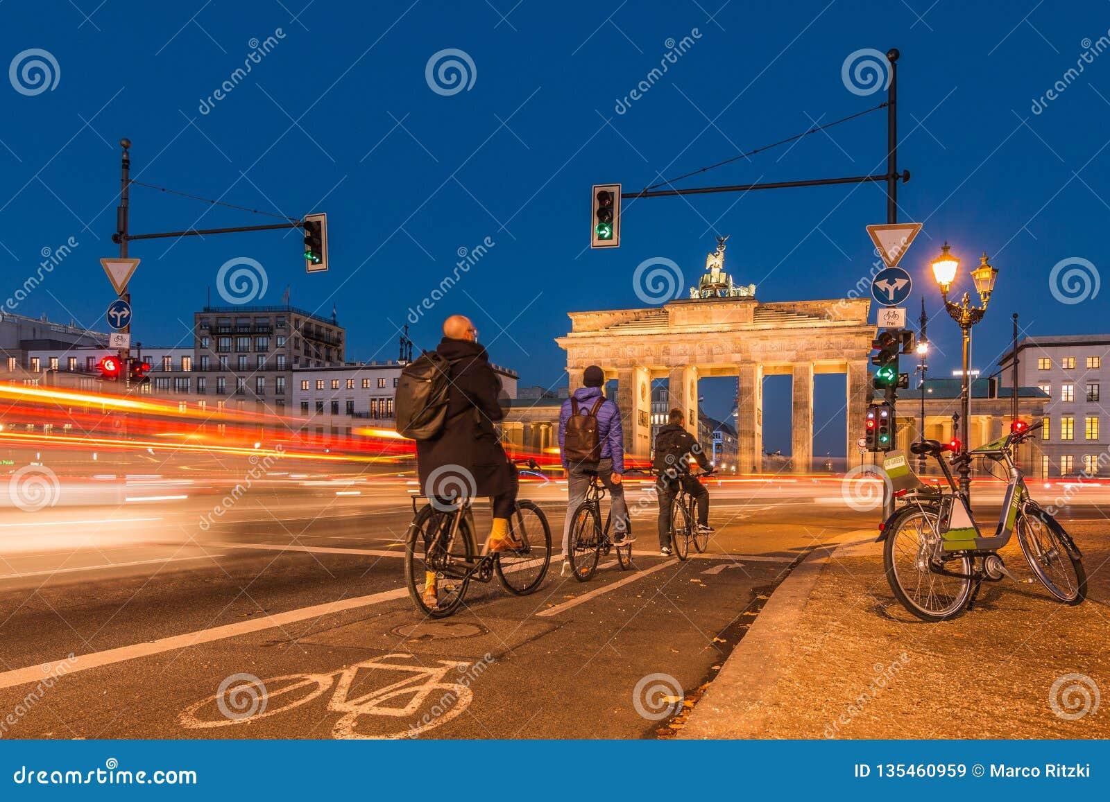 Porte de Brandebourg la nuit avec des cyclistes aux feux de signalisation