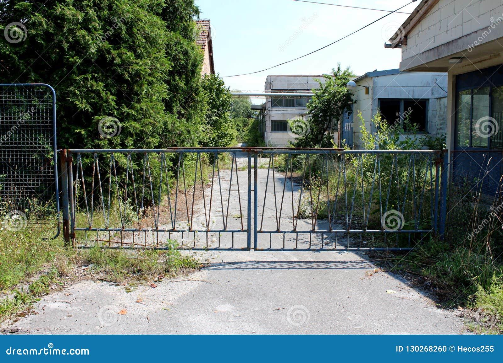 Porte del metallo arrugginite Locked che proteggono entrata alla fabbrica abbandonata con la strada privata completamente invasa