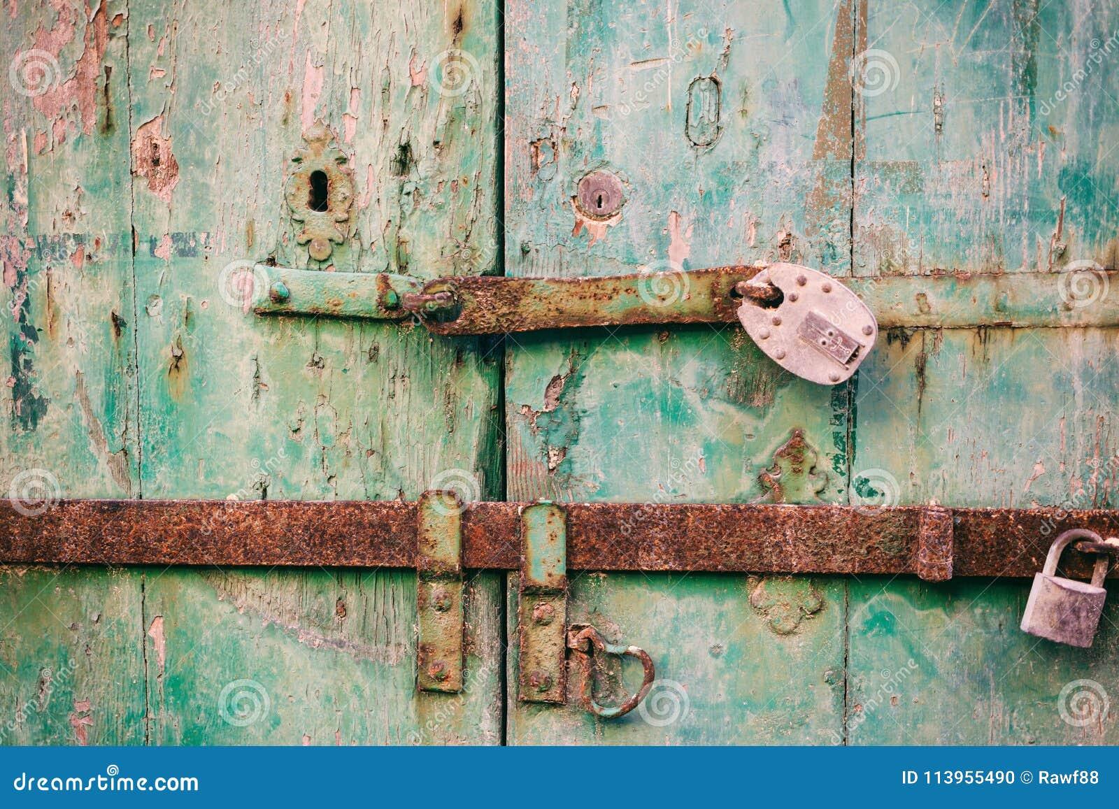 Portello Locked Vecchi lucchetti arrugginiti chiusi su una porta di legno afflitta