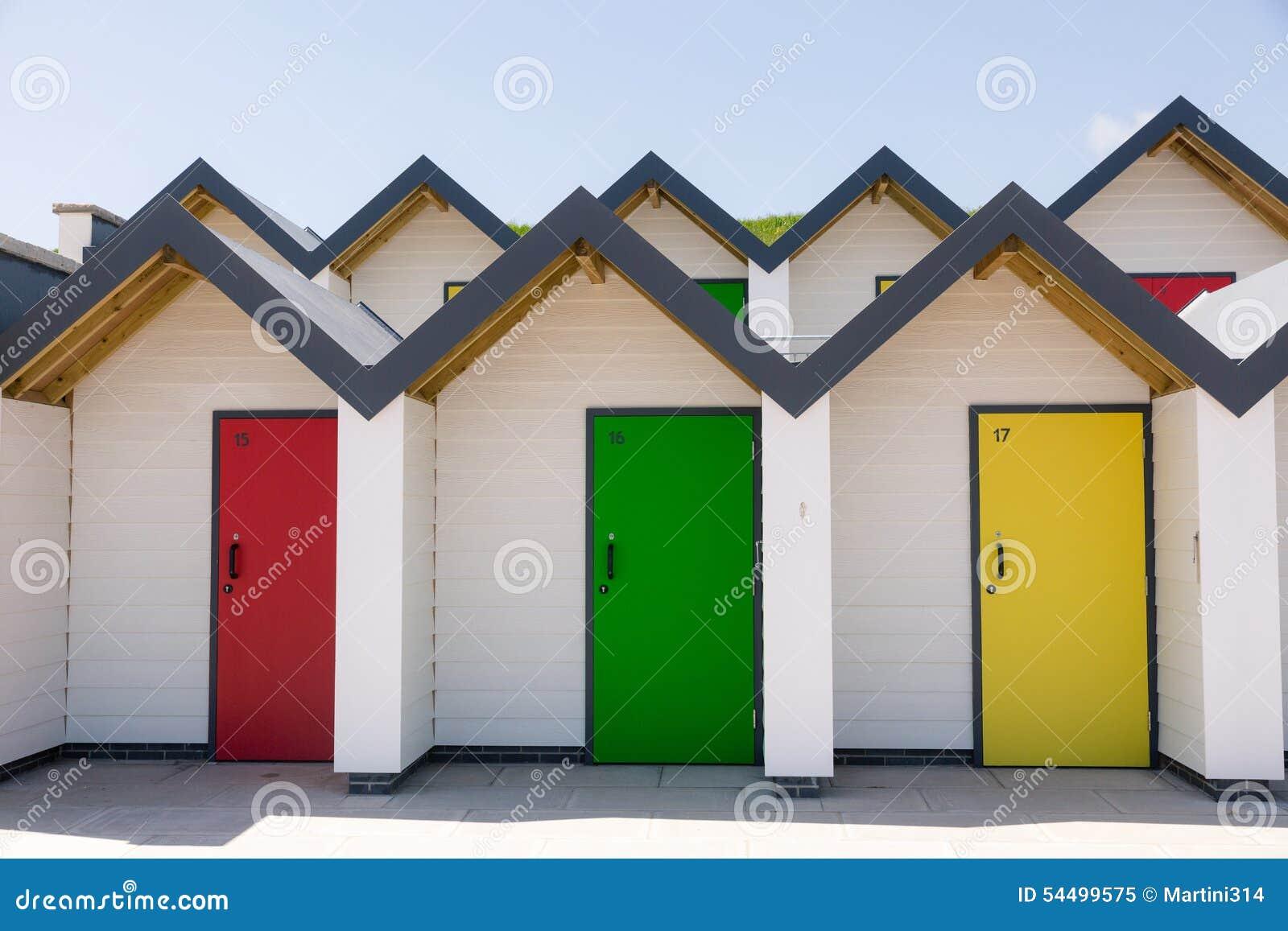 Portes colorées de jaune, de rouge et de vert, avec chacun étant numéroté individuellement, des maisons de plage blanches un jour