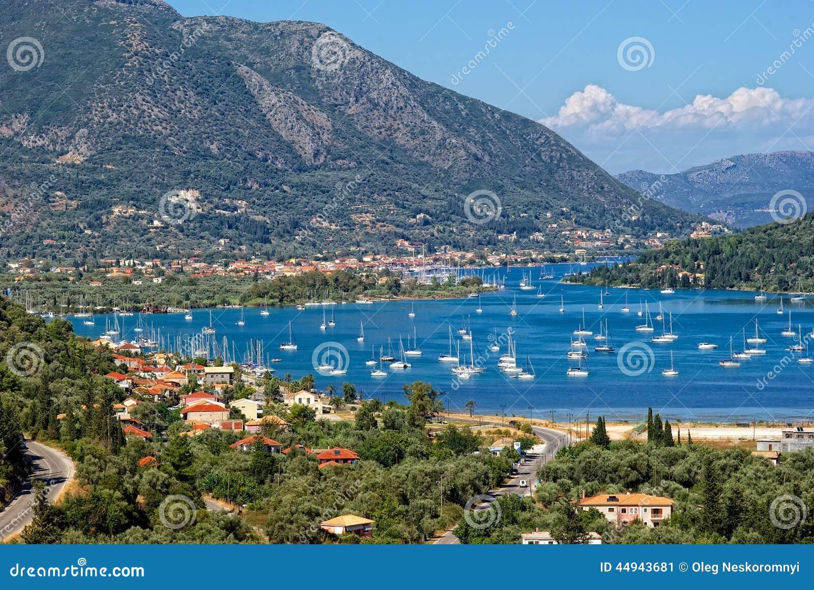Porto nelle montagne del fondo, l'isola di Nidri di Leucade, Grecia.