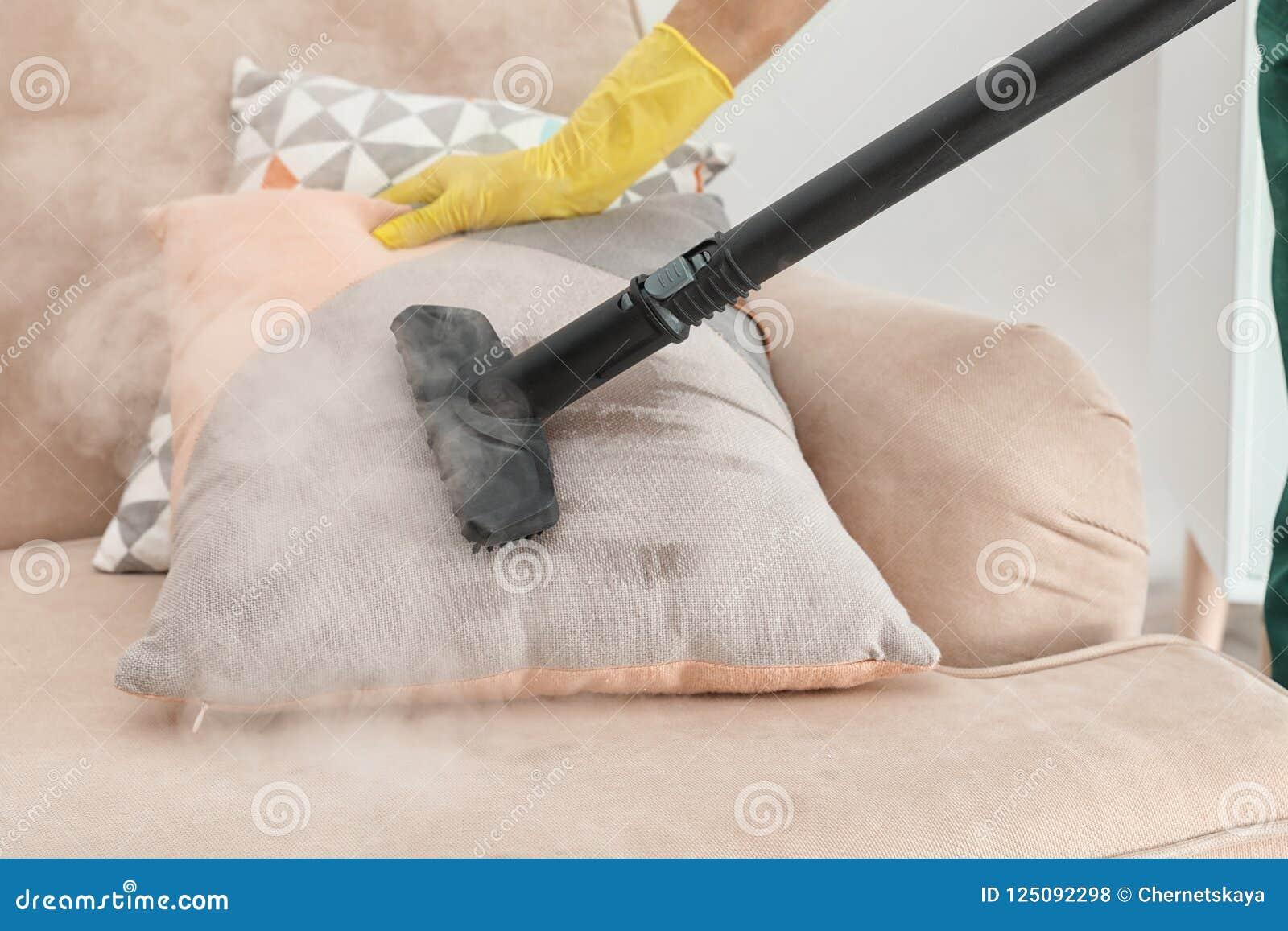 Portier enlevant la saleté du coussin de sofa avec le décapant de vapeur