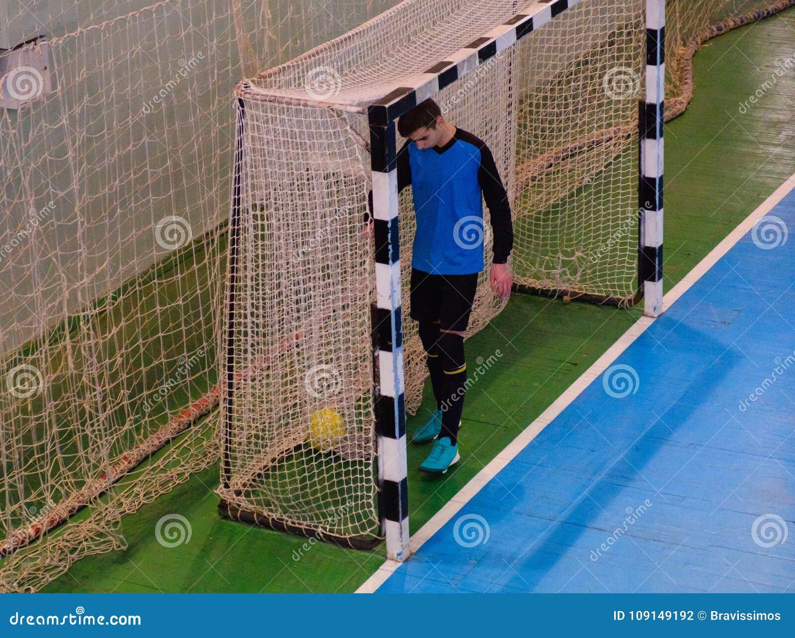Portiere di calcio sullo scopo, campo, campo di palla di Futsal nella palestra dell interno, campo di sport di calcio