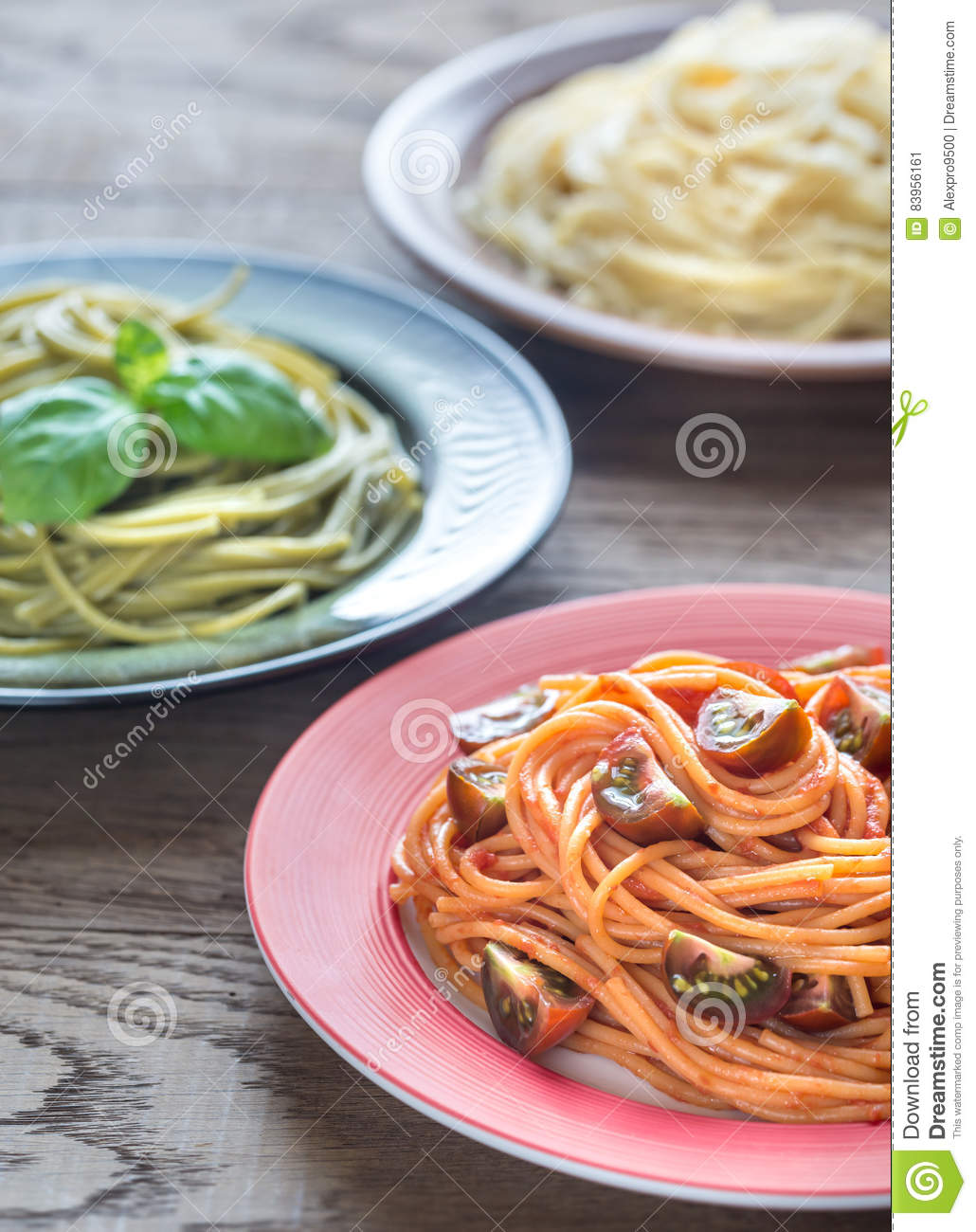Portions of colorful spaghetti with ingredients