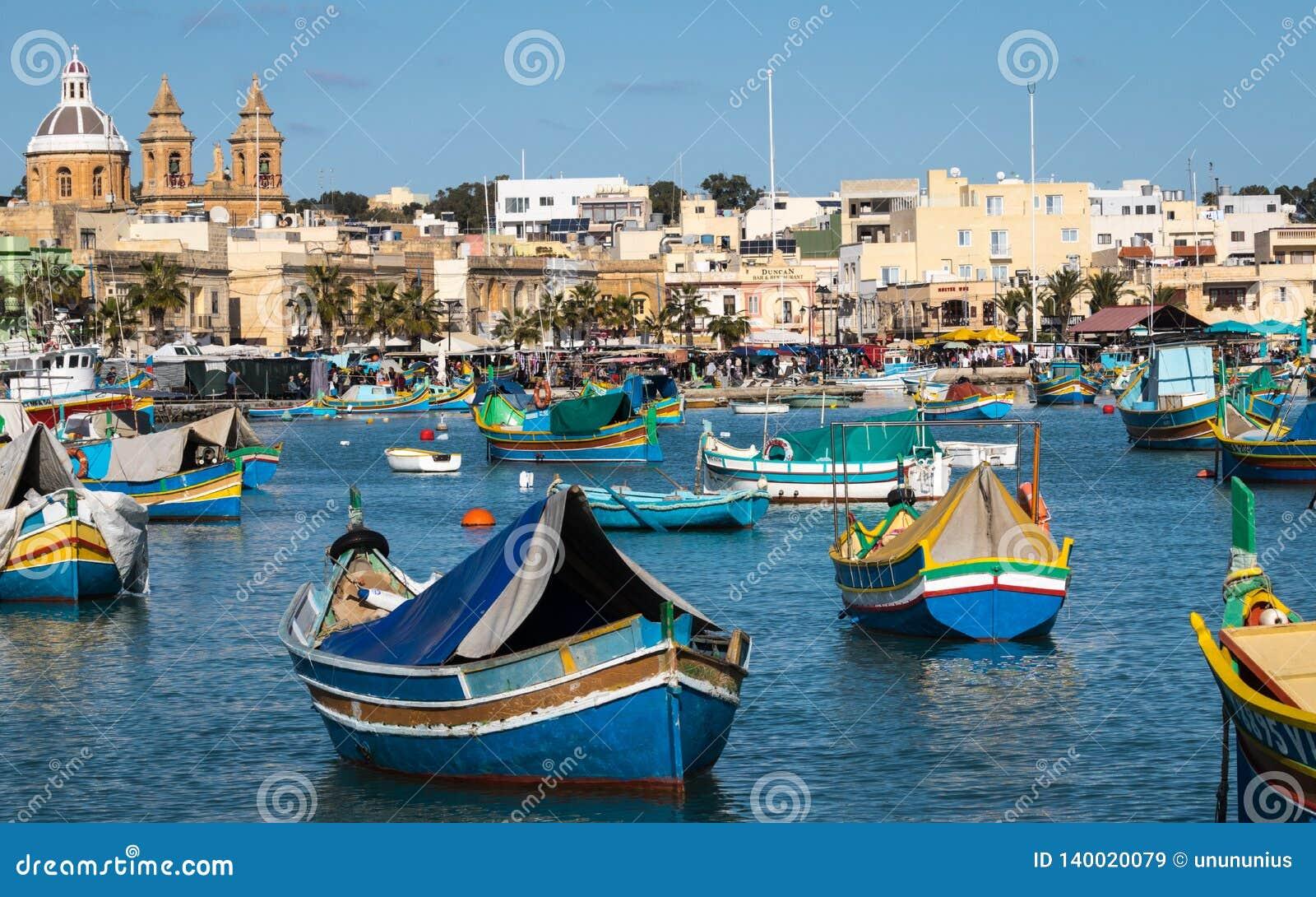 Porto de Marsaxlokk com os barcos tradicionais, coloridos de Luzzu na baía com mercado do fundo