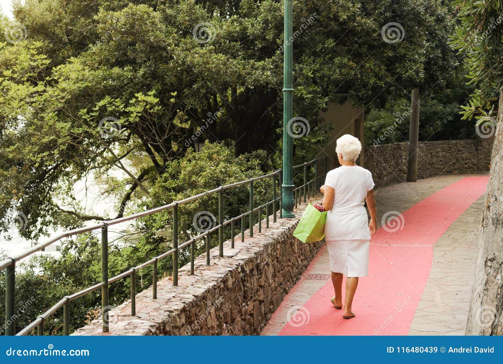 Portofino, Italië, 19 Juli, 2017: Bejaarde die op de straat weggaan