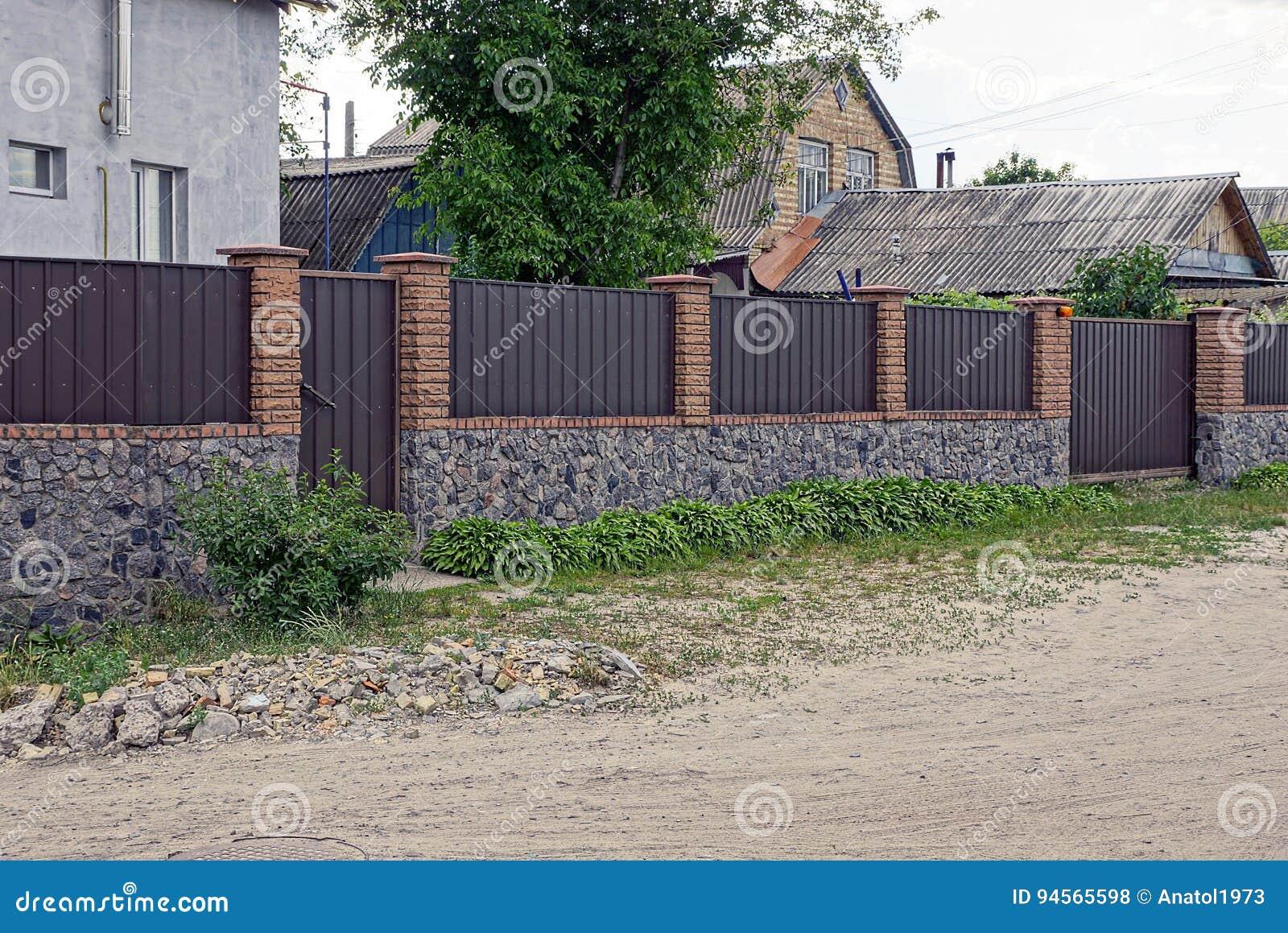 Portone marrone di pietra del ferro e del recinto su una via rurale