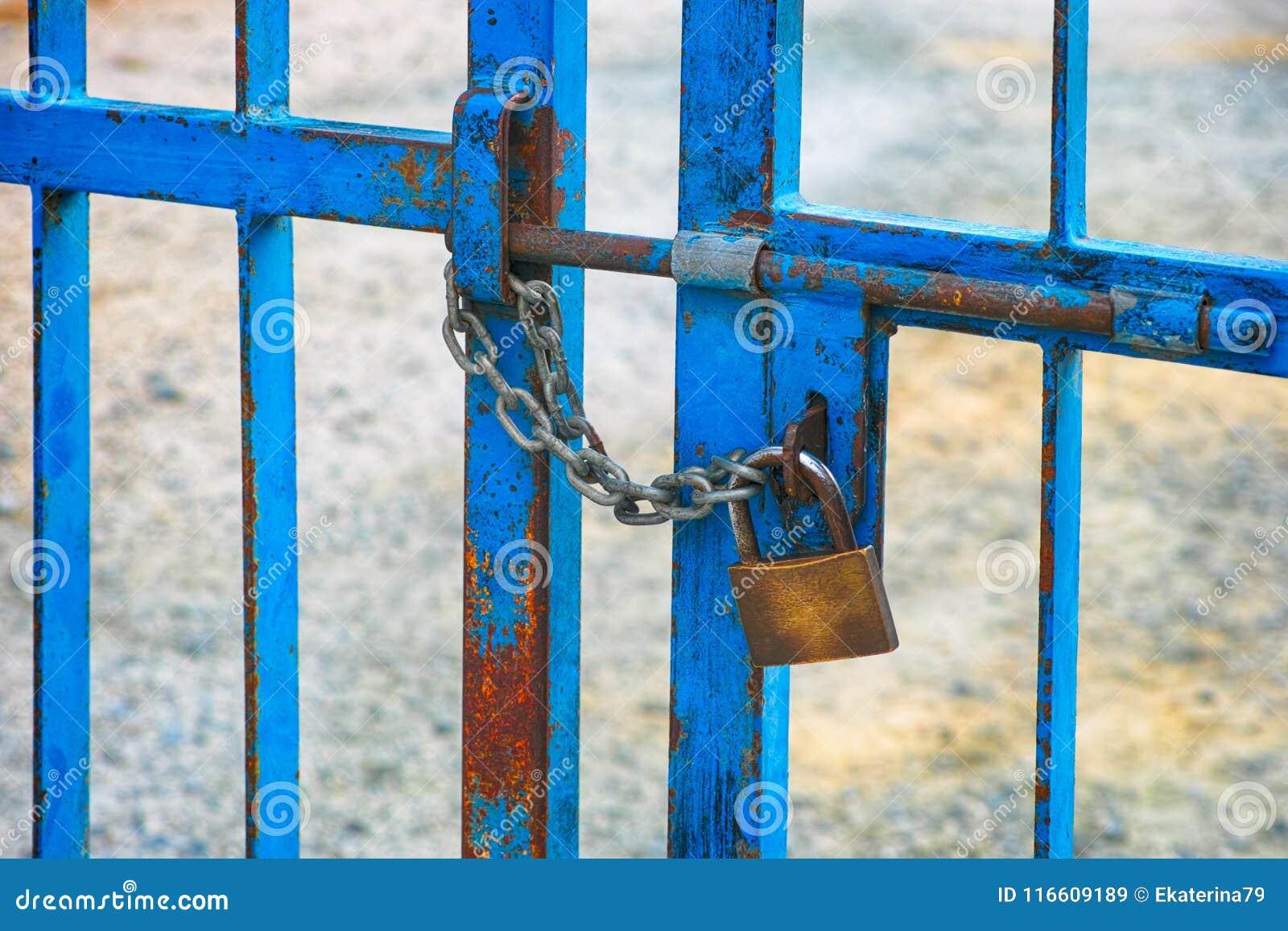 Portoni del recinto del metallo con il bullone ed il lucchetto