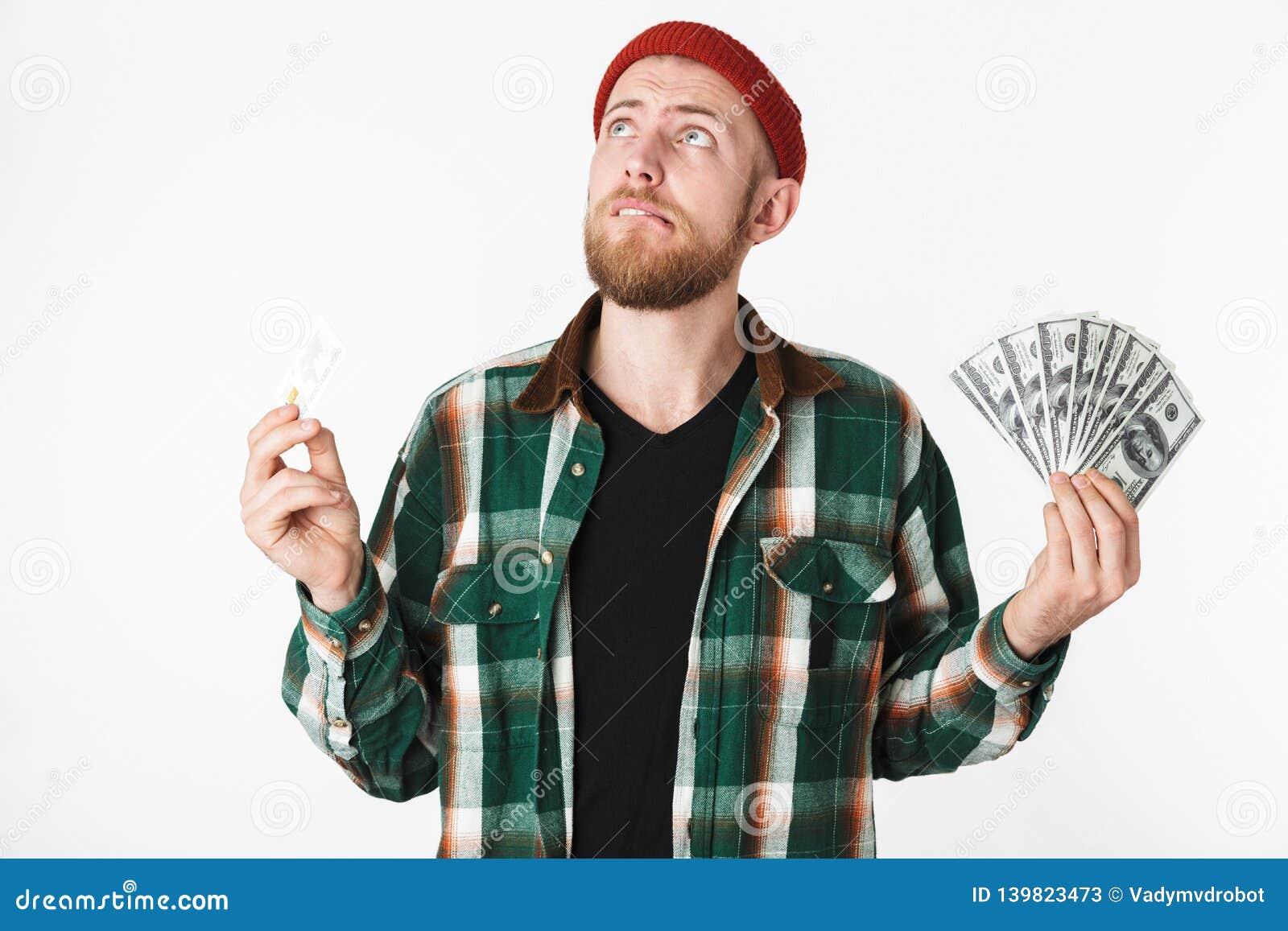 Porträt der Hippie-Mannholdingkreditkarte und Fan des Dollargeldes, bei der Stellung lokalisiert über weißem Hintergrund