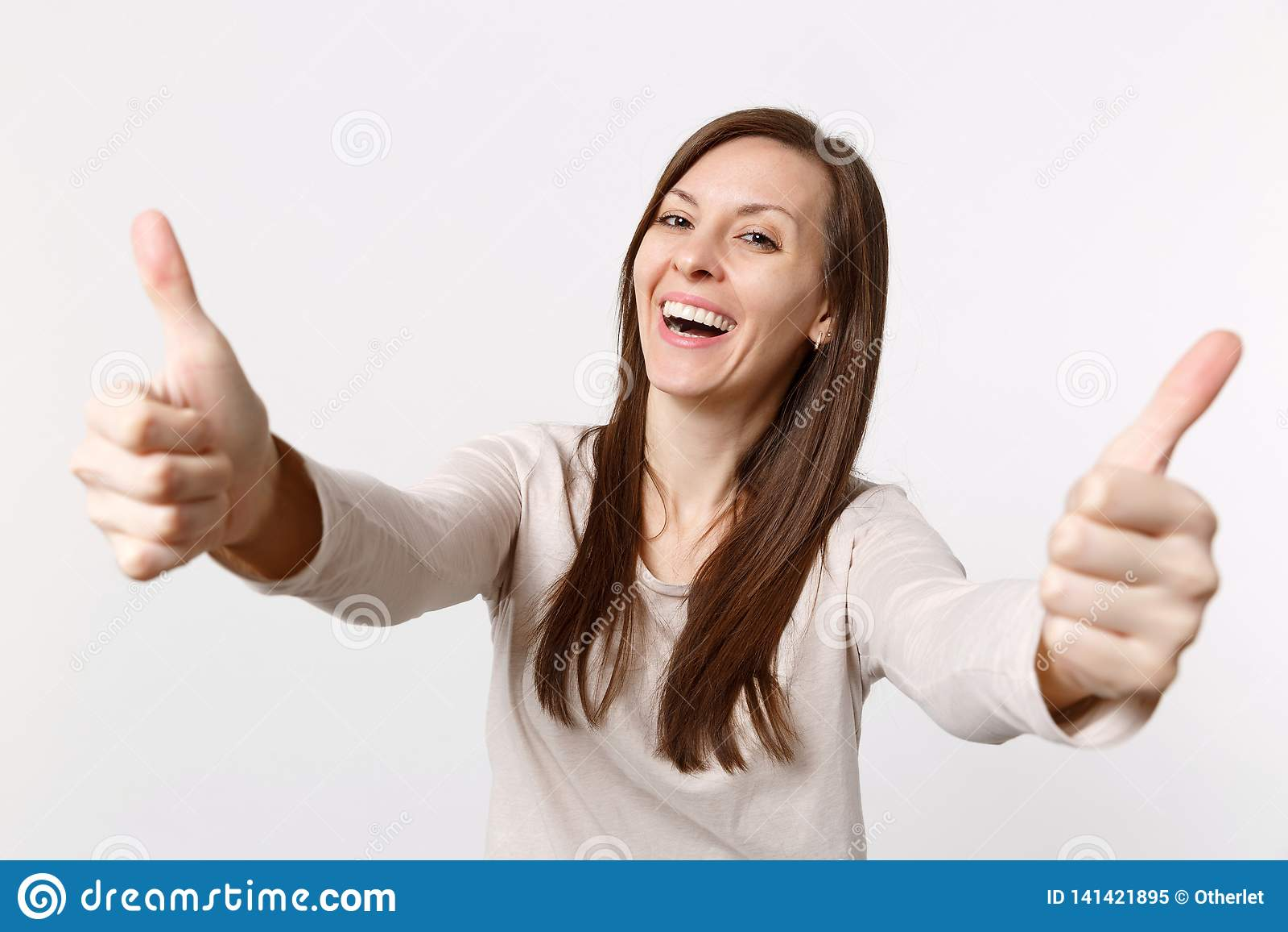 Porträt der lächelnden lachenden attraktiven jungen Frau in der hellen Kleidung, welche die Daumen oben lokalisiert auf weißem Wa