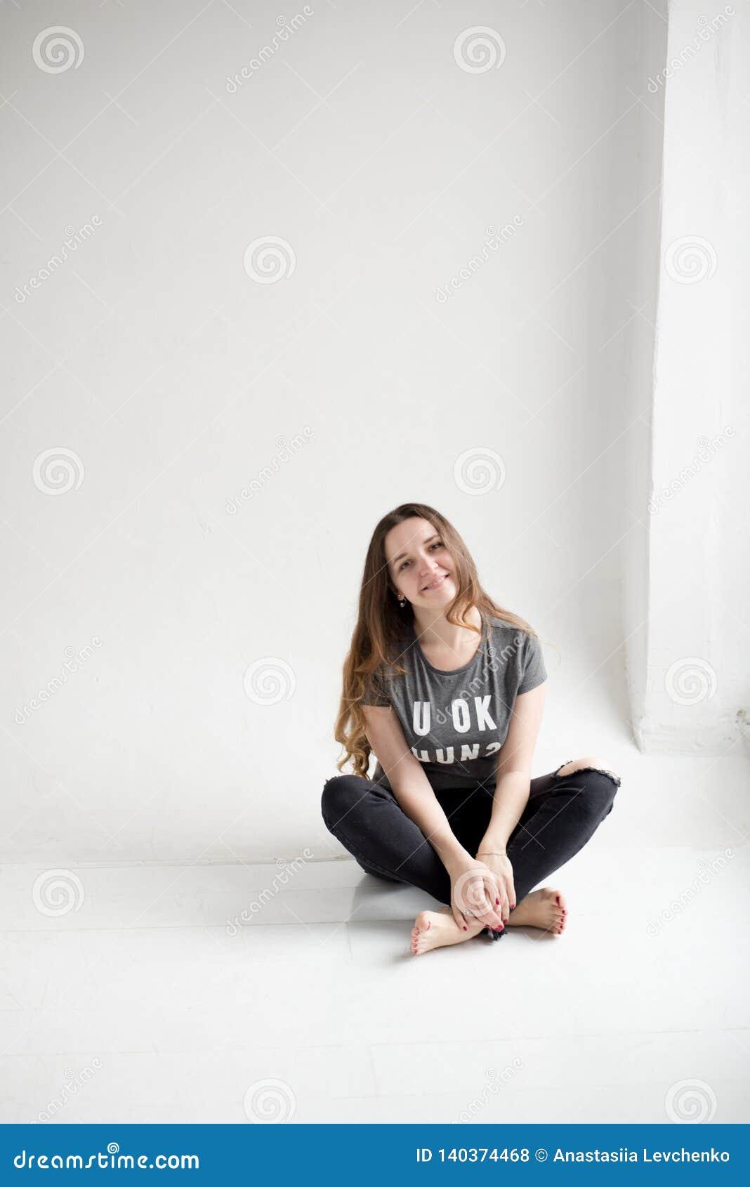 Porträt eines lächelnden jungen Mädchens, das mit den Beinen gekreuzt lokalisiert auf weißem Hintergrund sitzt
