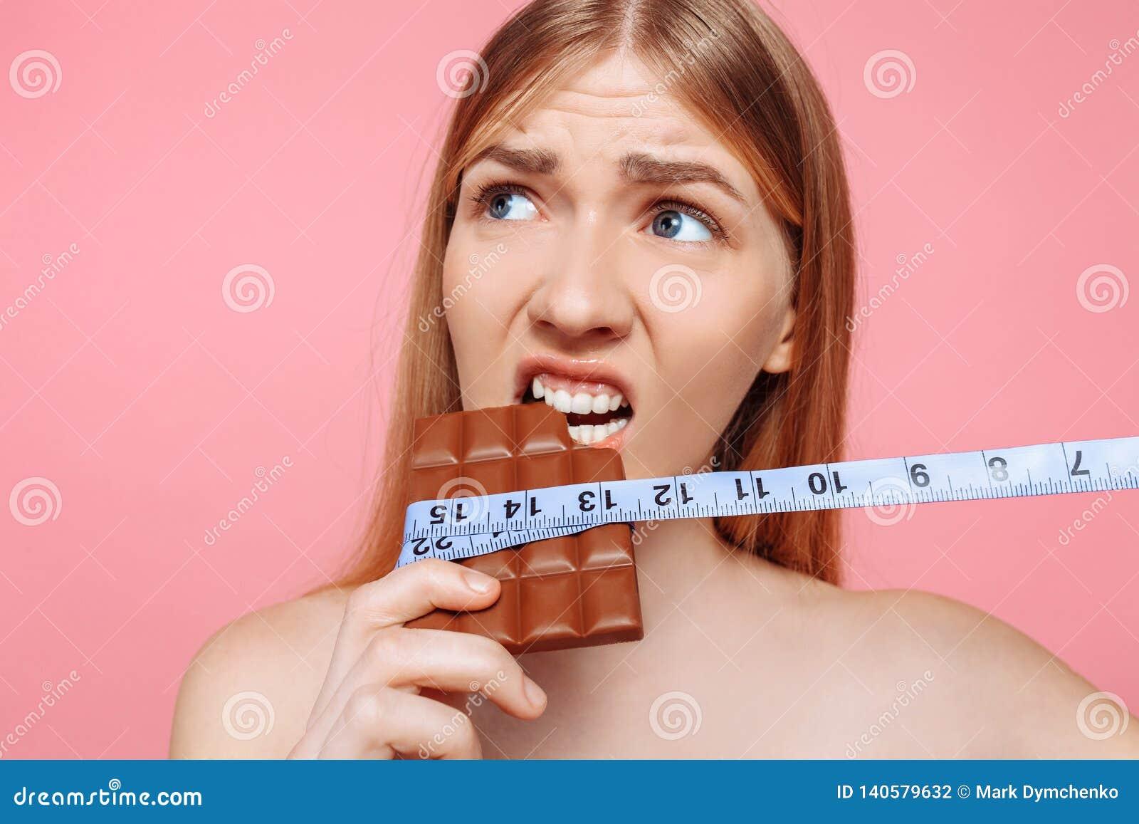 Porträt eines nachdenklichen Mädchens, das eine Schokolade eingewickelt mit einem Maßband auf einem rosa Hintergrund beißt