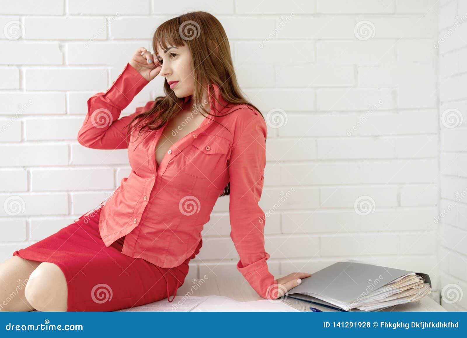 Porträt eines schönen Empfangsdamengeschäftsmädchens, das am Schreibtisch auf einem weißen Hintergrund sitzt