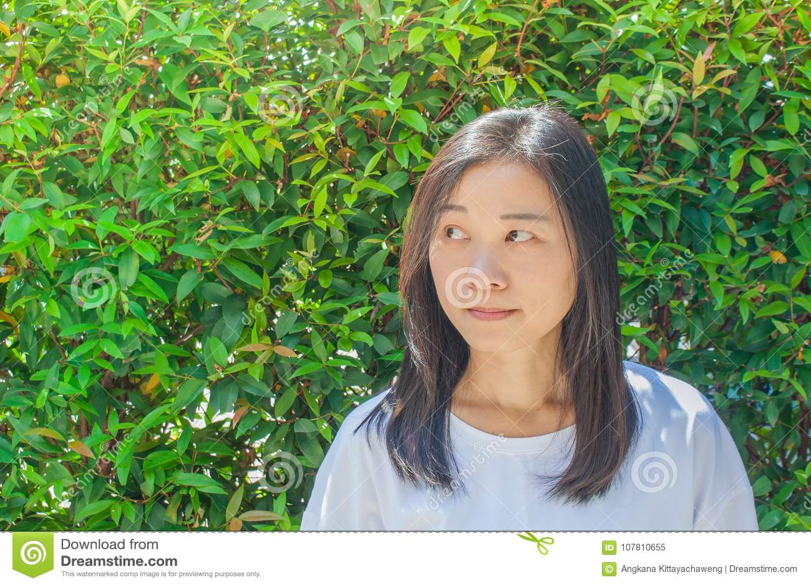 Porträt-Asiatin tragendes Whitt-shirt und Denken etwas Sie Hand der rechten Seite betrachtend