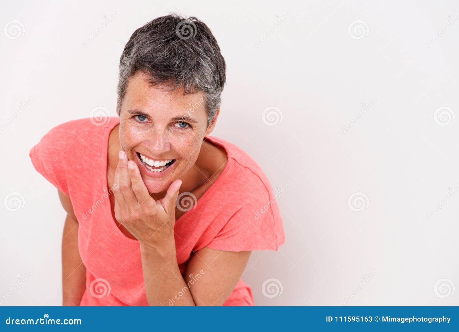 Porträt der älteren Frau lachend gegen weißen Hintergrund