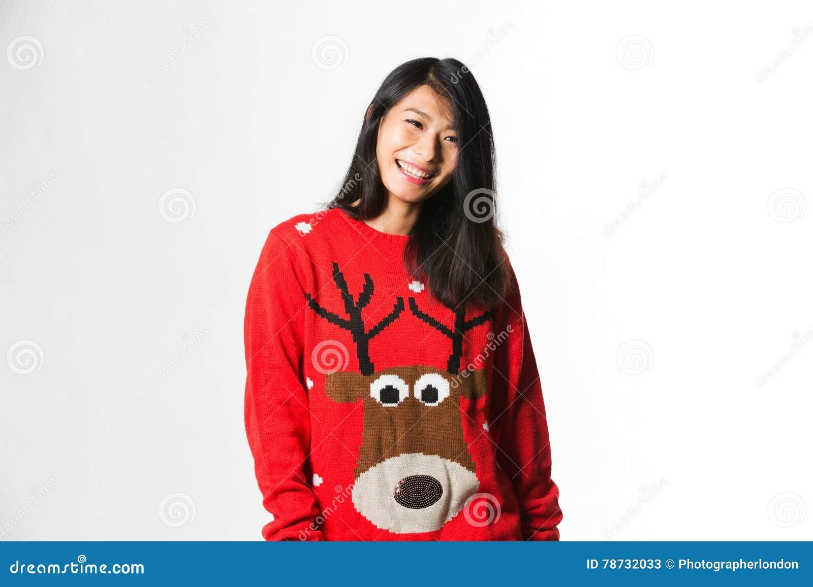 Porträt der Chinesin in der Weihnachtsstrickjacke, die vor grauem Hintergrund steht